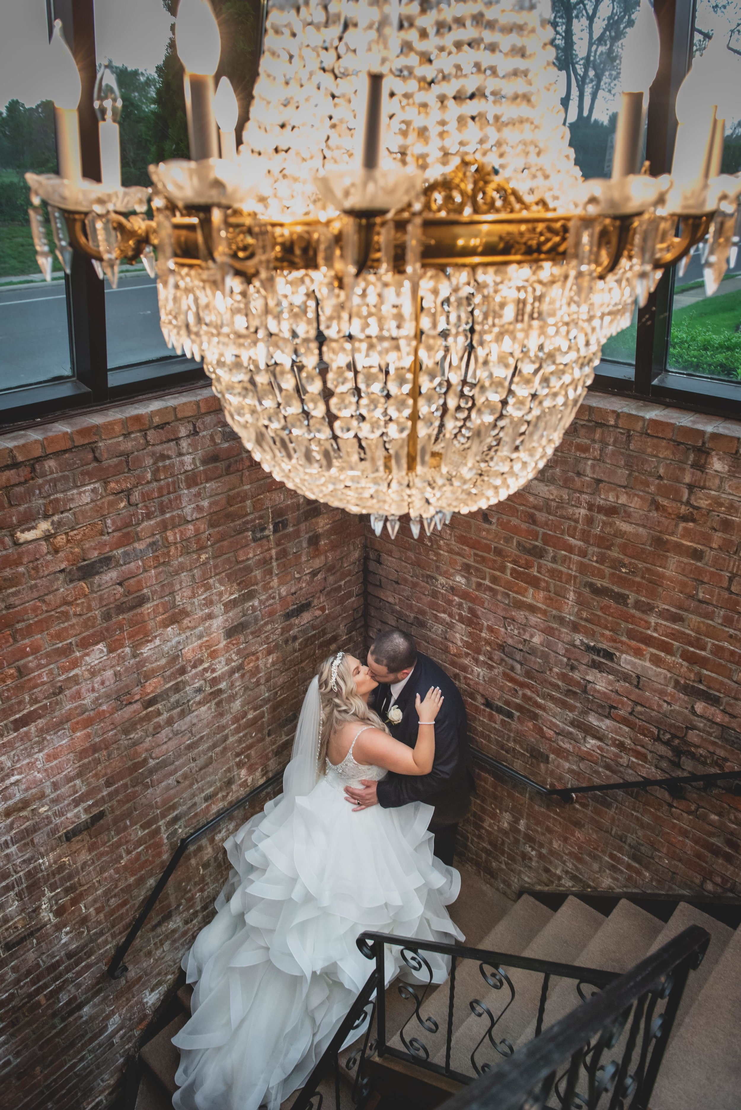 Bride and groom kissing under an extravagant chandelier.