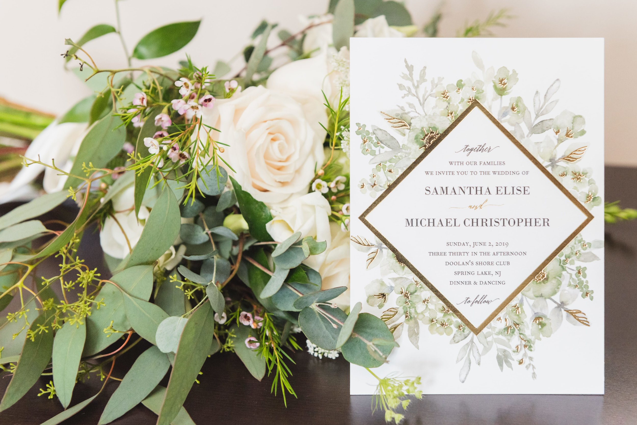 A wedding invitation decorated with lush greenery and white roses next to an identical centerpiece.