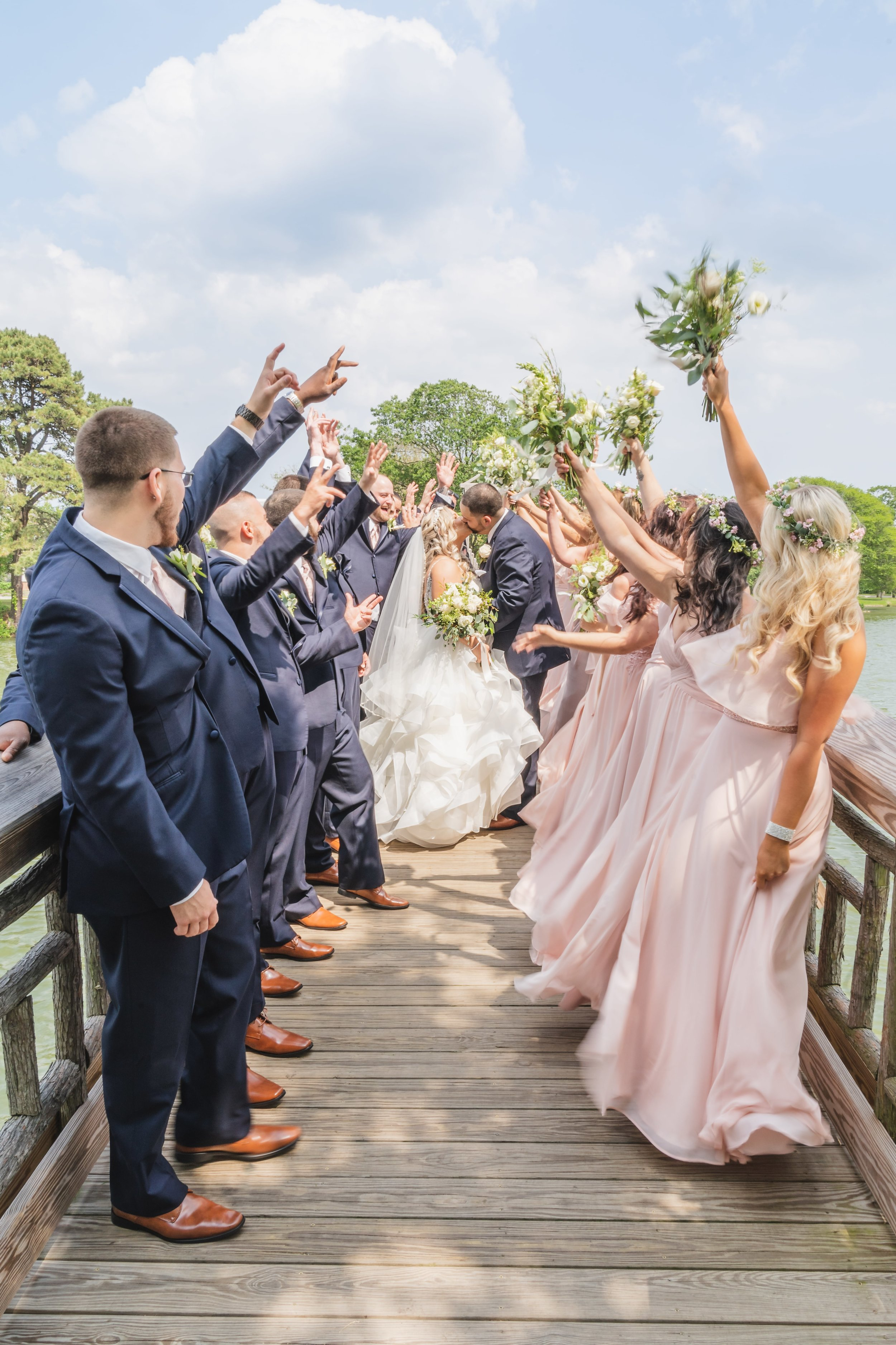 Bridal party lining a pier on either side of the of the bride and groom as they share a kiss as a married couple.