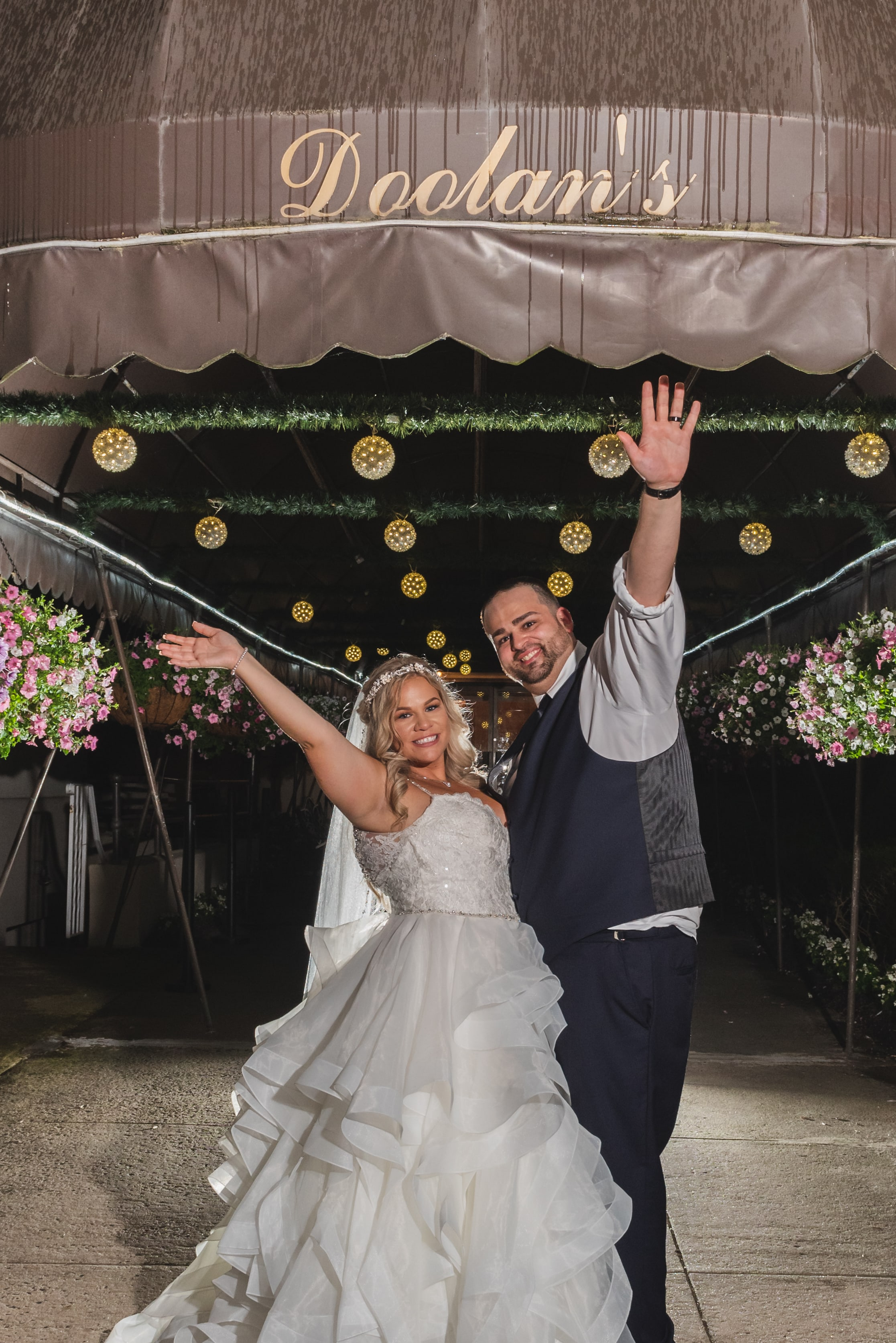 The bride and groom raising their arms in celebration in front of their reception venue.