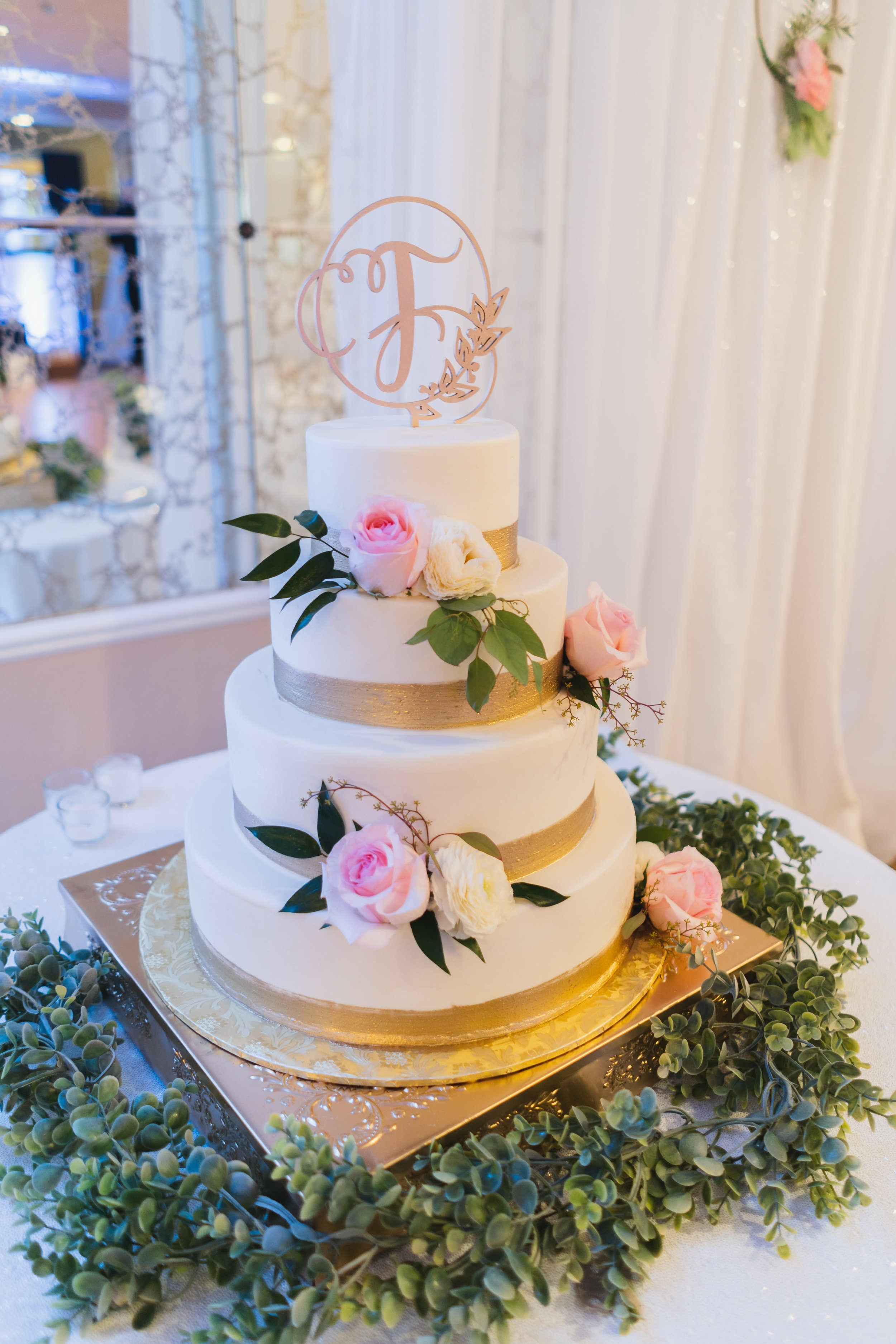 A white wedding cake adorned with pink and white roses.