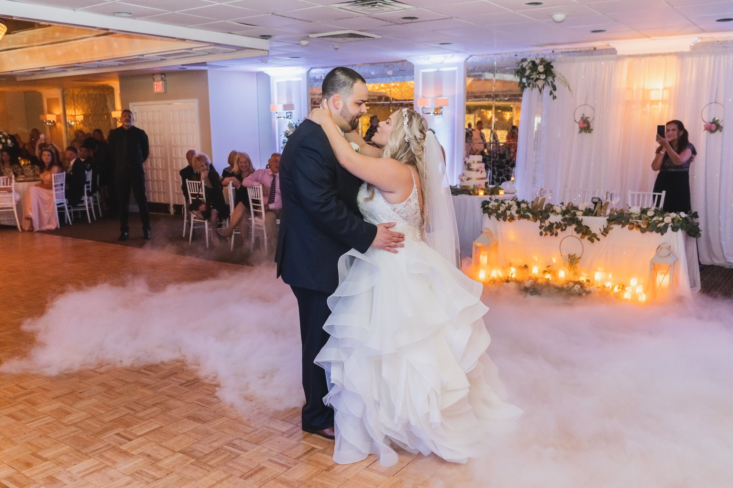Bride and groom sharing the first dance on a fog filled venue dance floor.