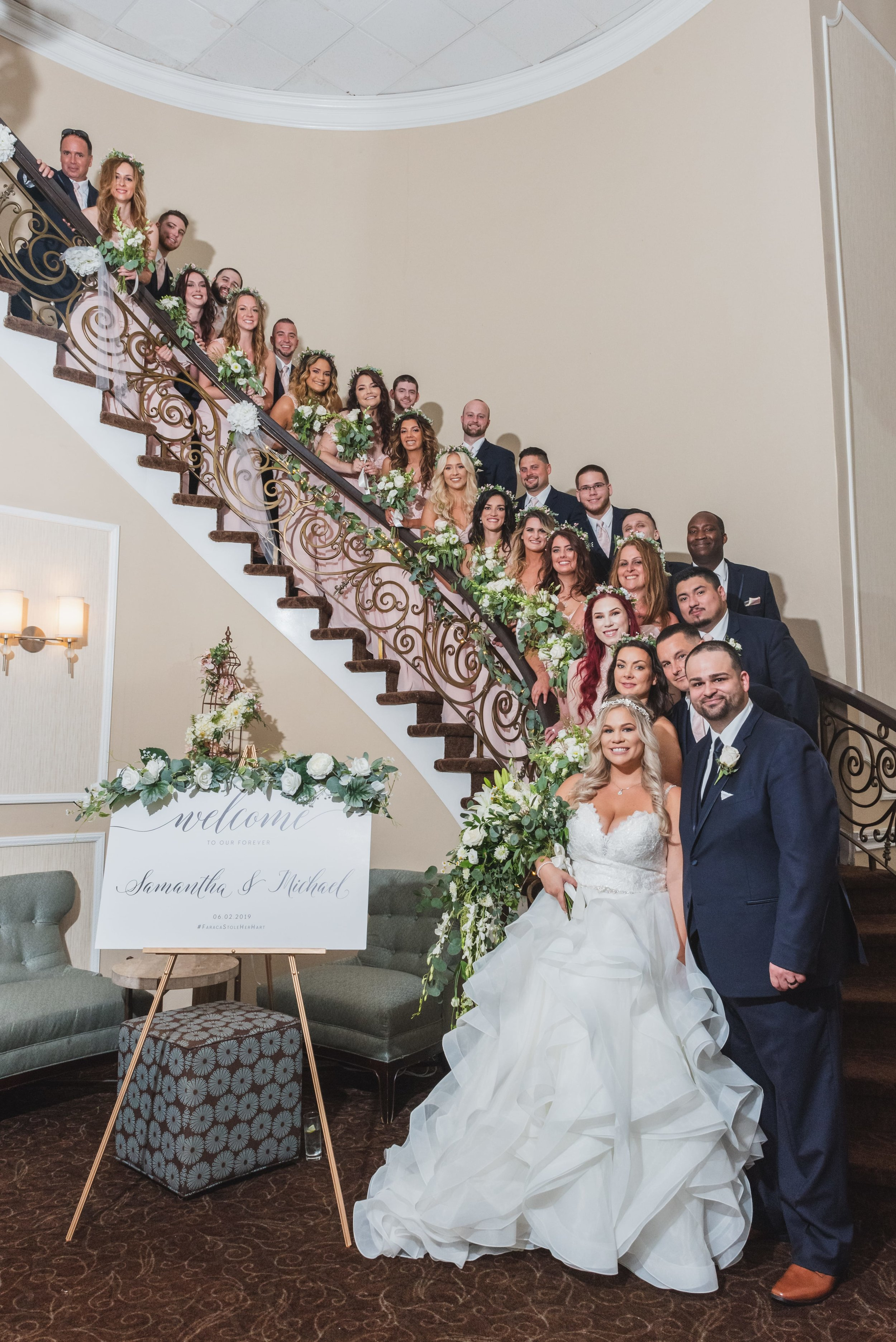 A large bridal party lining a curving staircase from top to bottom.
