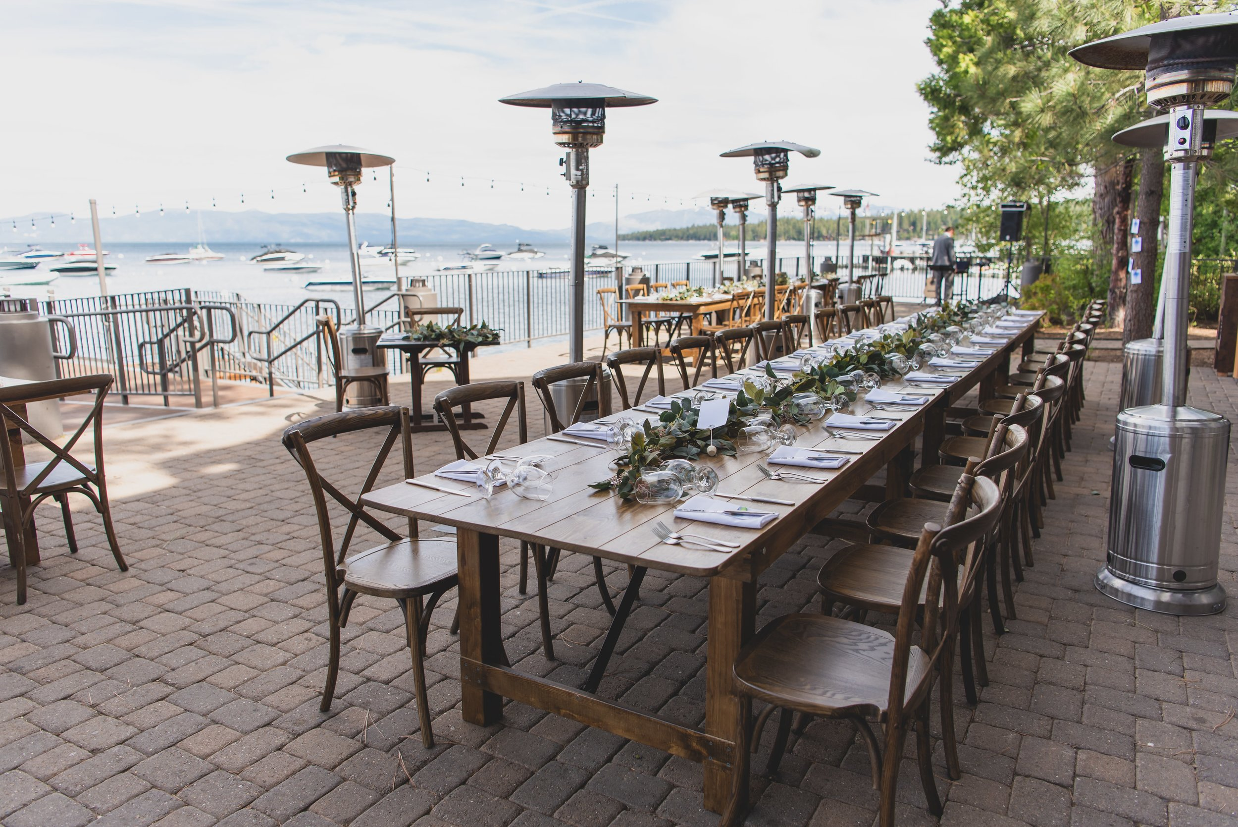 Last Minute Checklist: Things to Know Before Your Outdoor Wedding - An outdoor reception with long wooden tables flanked by heat lamps.