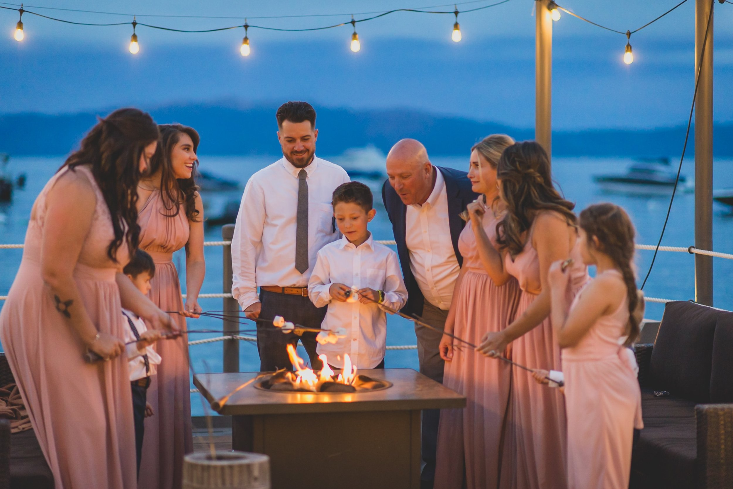 Last Minute Checklist: Things to Know Before Your Outdoor Wedding - The bridal party roasting marshmallows at an outdoor fire pit during an evening wedding reception.