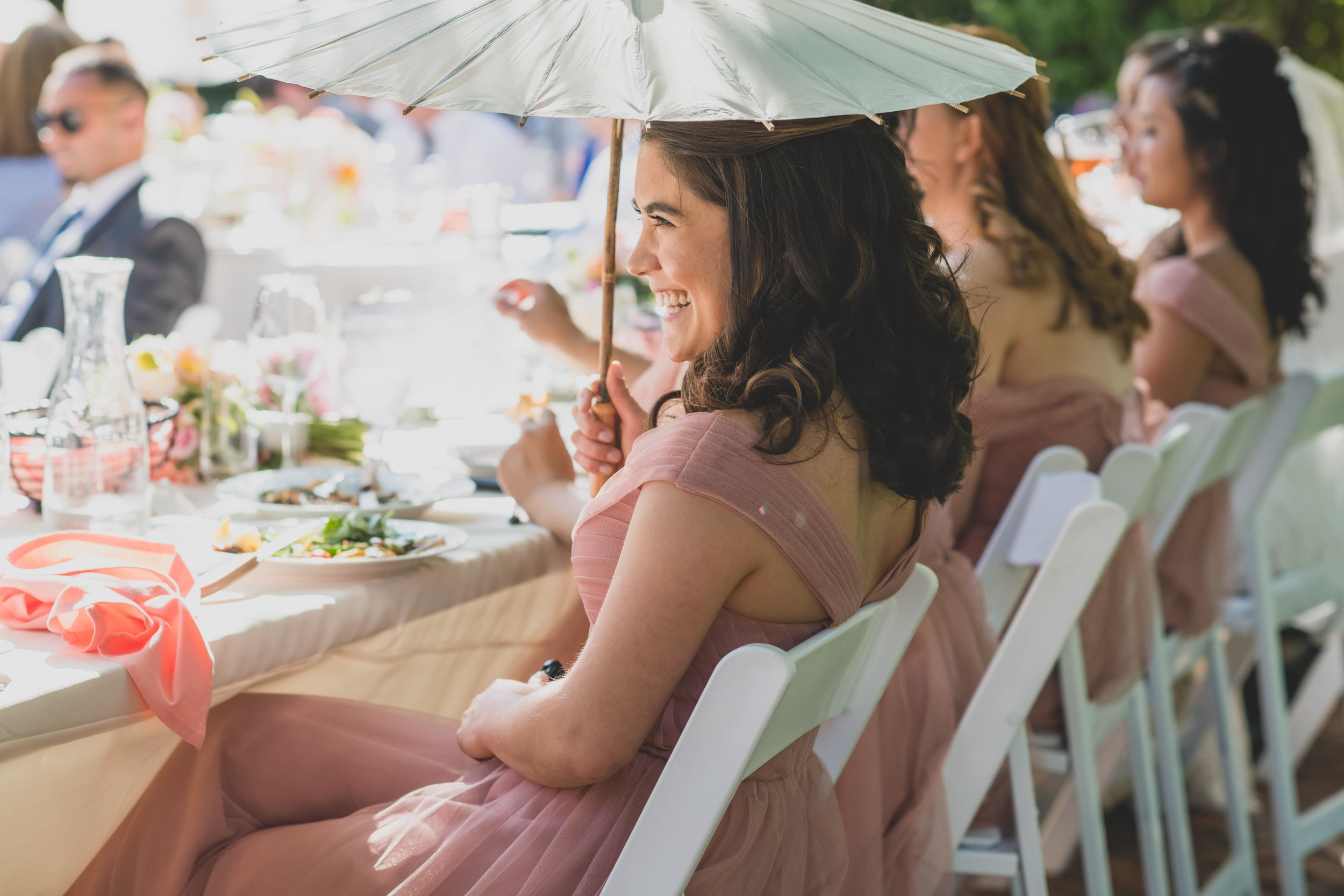 Last Minute Checklist: Things to Know Before Your Outdoor Wedding - A bridesmaid using a parasol to shield herself from the summer heat during an outdoor wedding reception.