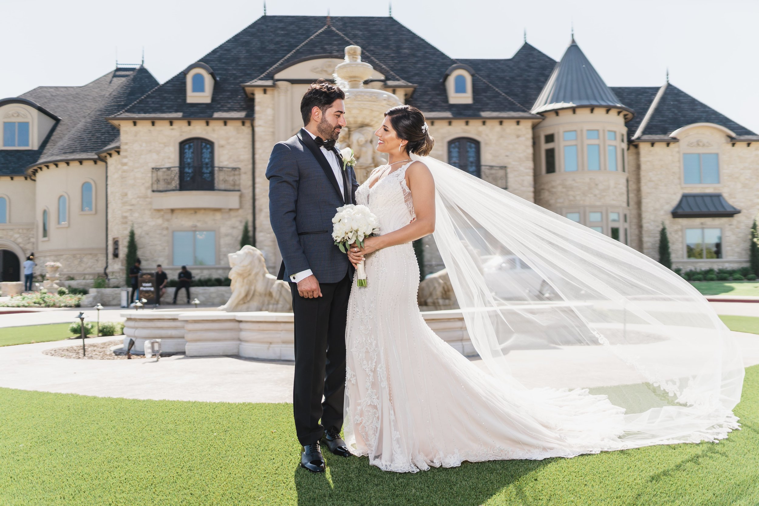 Bride with wind-blown veil facing her groom in front of a mansion.