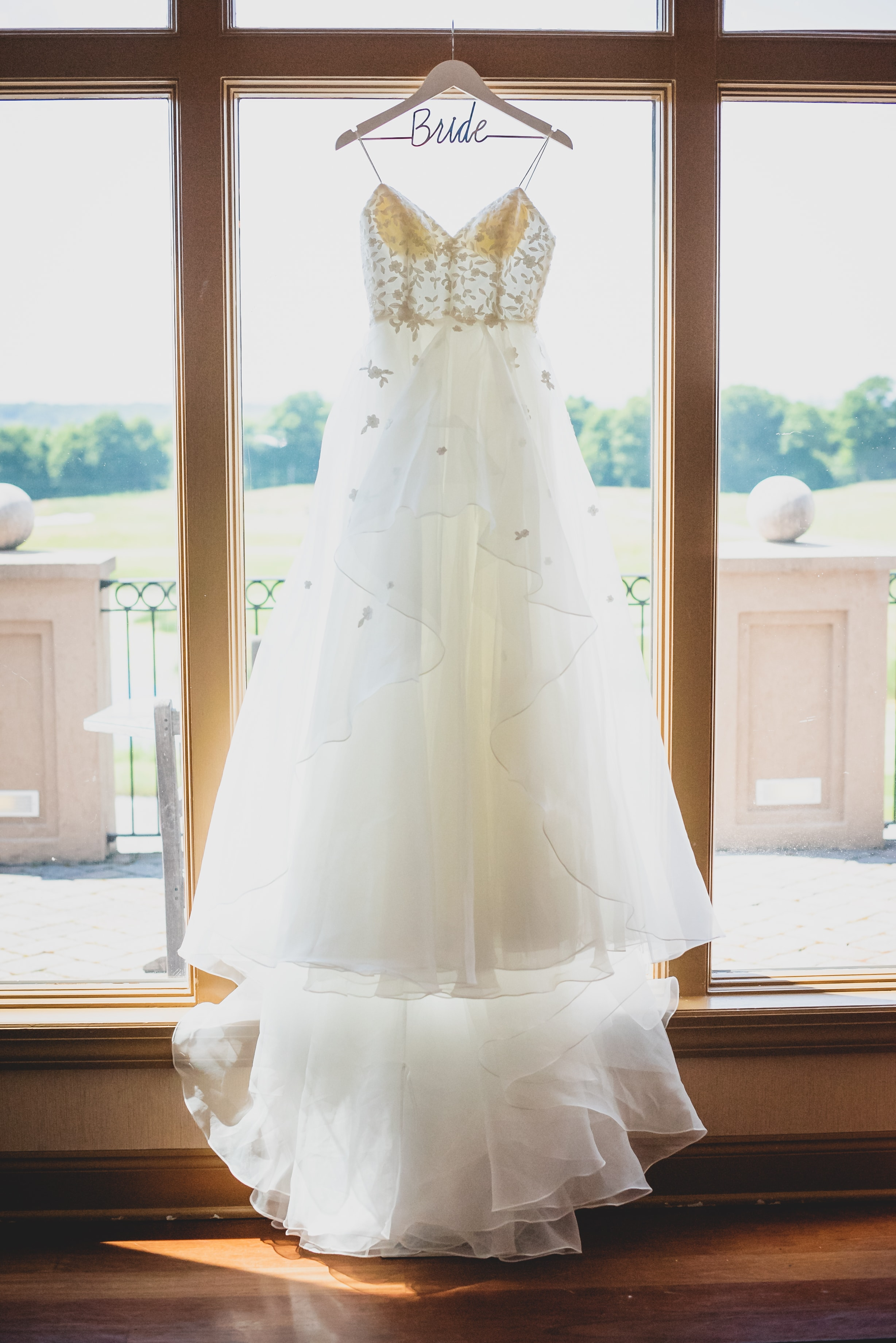 White flowing wedding dress hanging from a window sill in a wooden room.