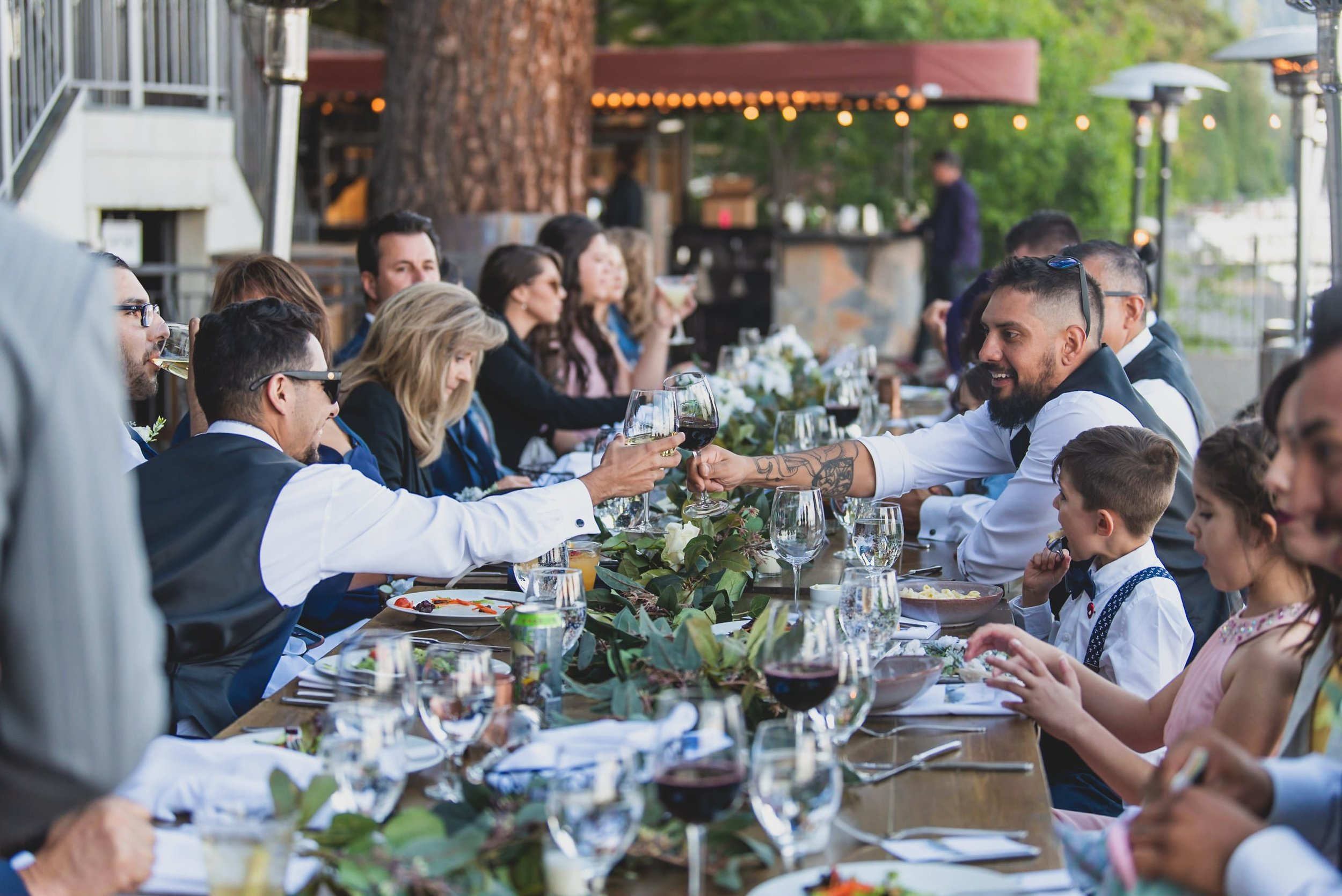 Wedding guests celebrate at an outdoor reception sitting at a long wooden table.