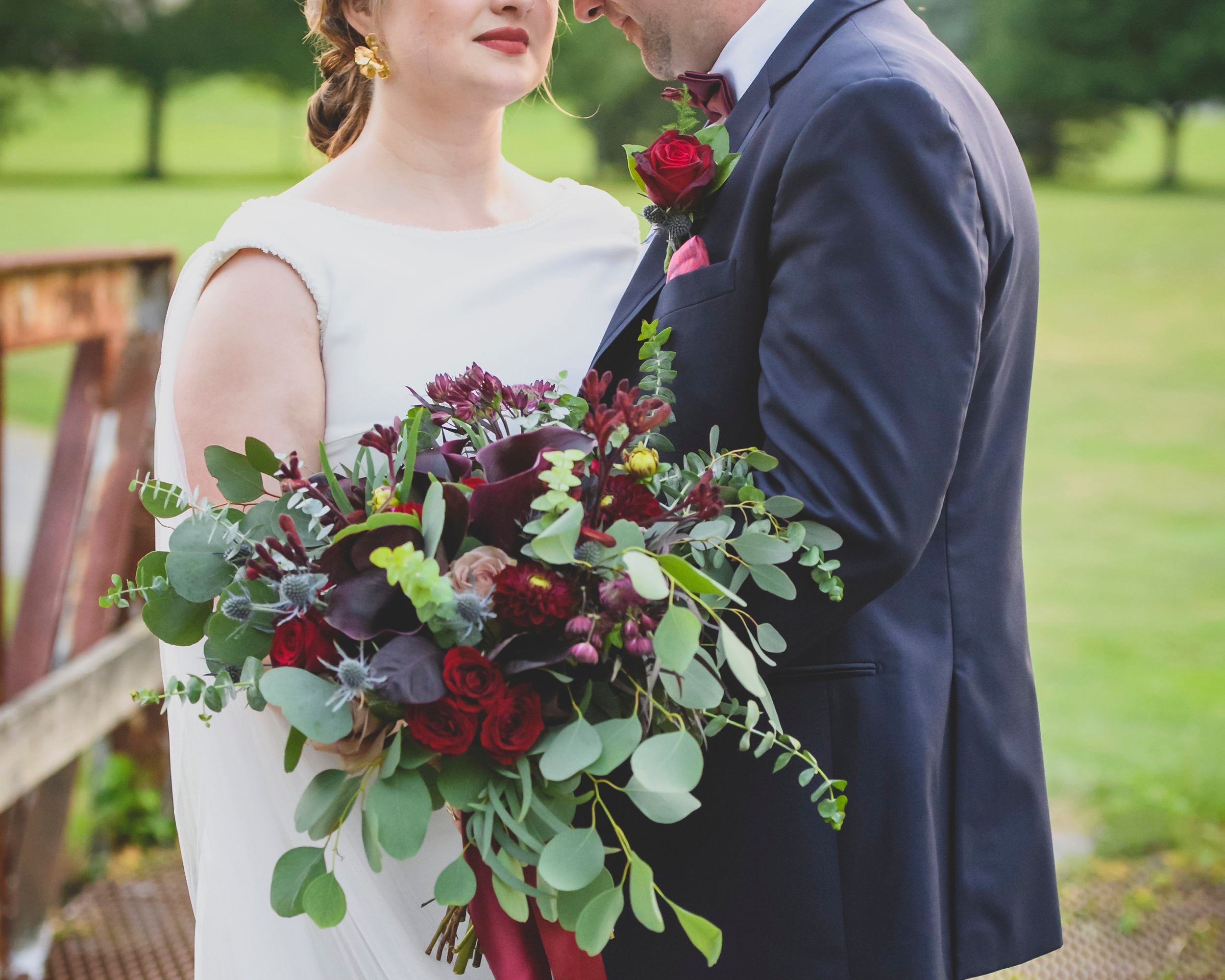Bride and groom holding a seasonal fall bouquet with natural greens and deep red roses.