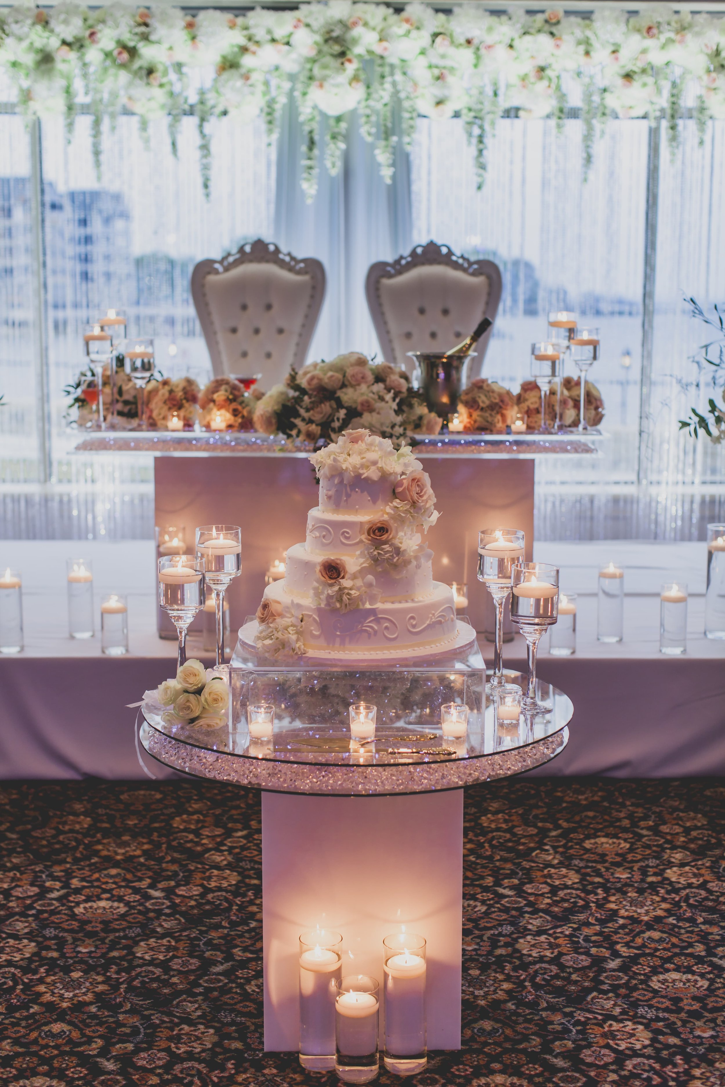 A flowered wedding cake on a glass table surrounded by floating candles.