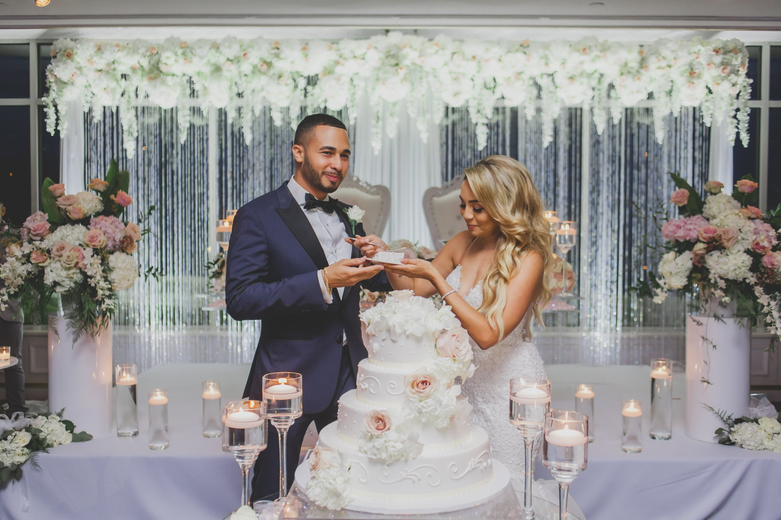 A bride and groom exchanging bites of wedding cake flanked by floating candles and flowers.