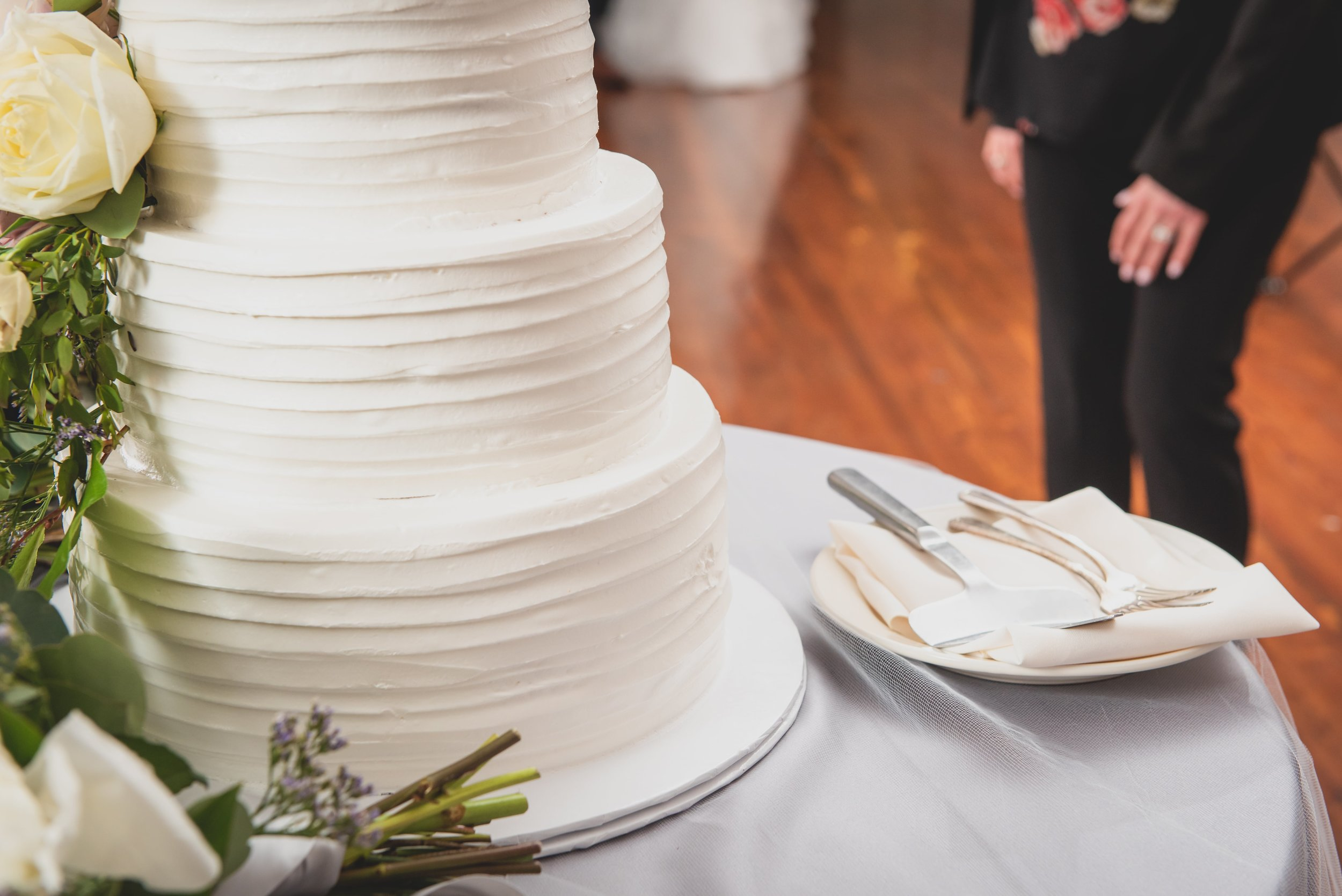 A close up of a wedding cake with the serving knife and two forks at the ready.