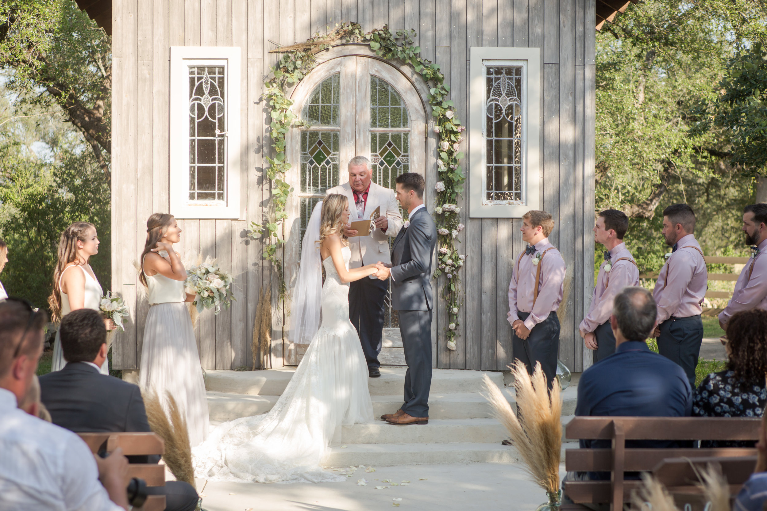 An outdoor wedding ceremony at a small countryside chapel.