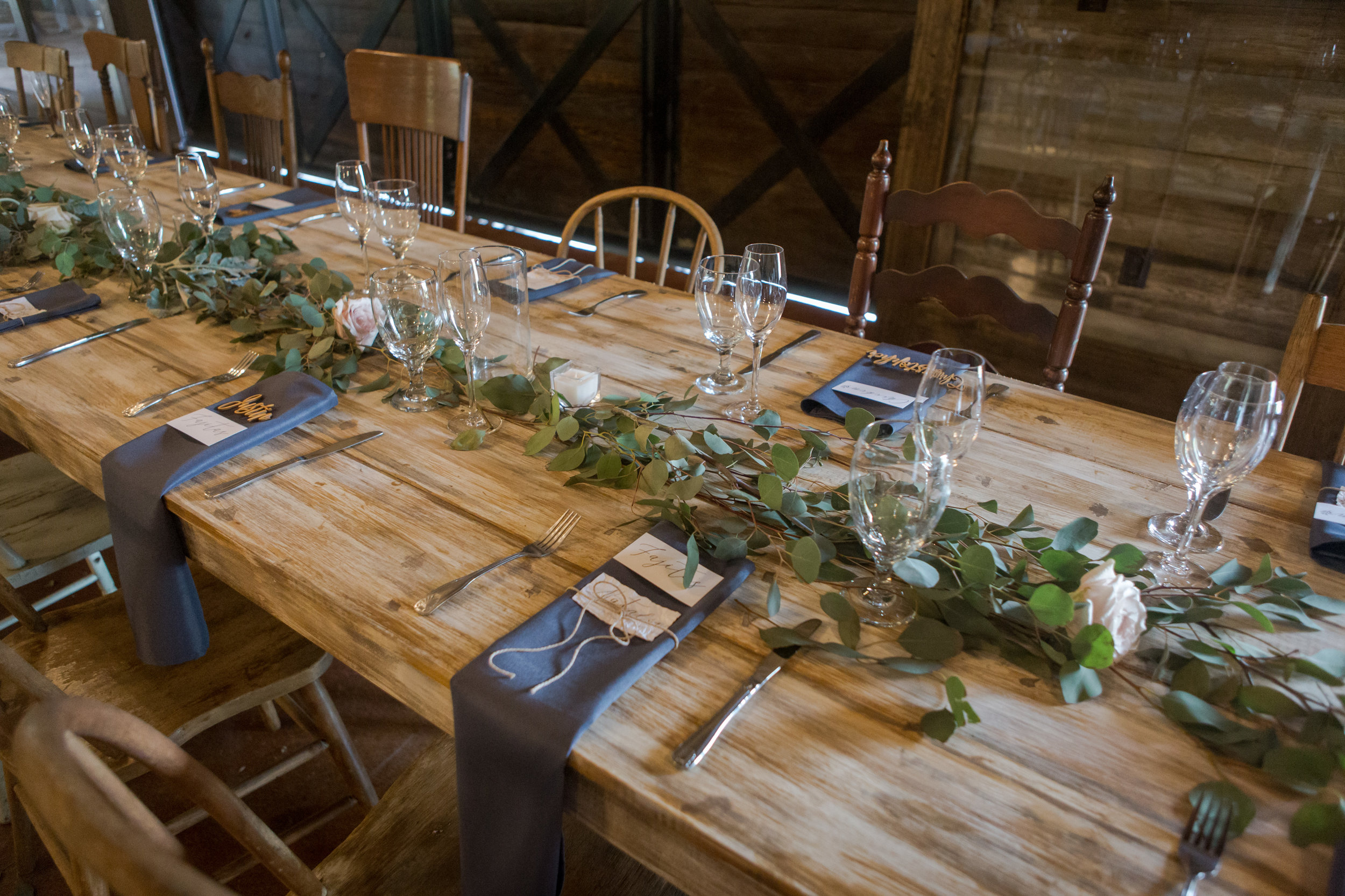 Long wooden wedding reception tables decorated with eucalyptus runners and jute twine.