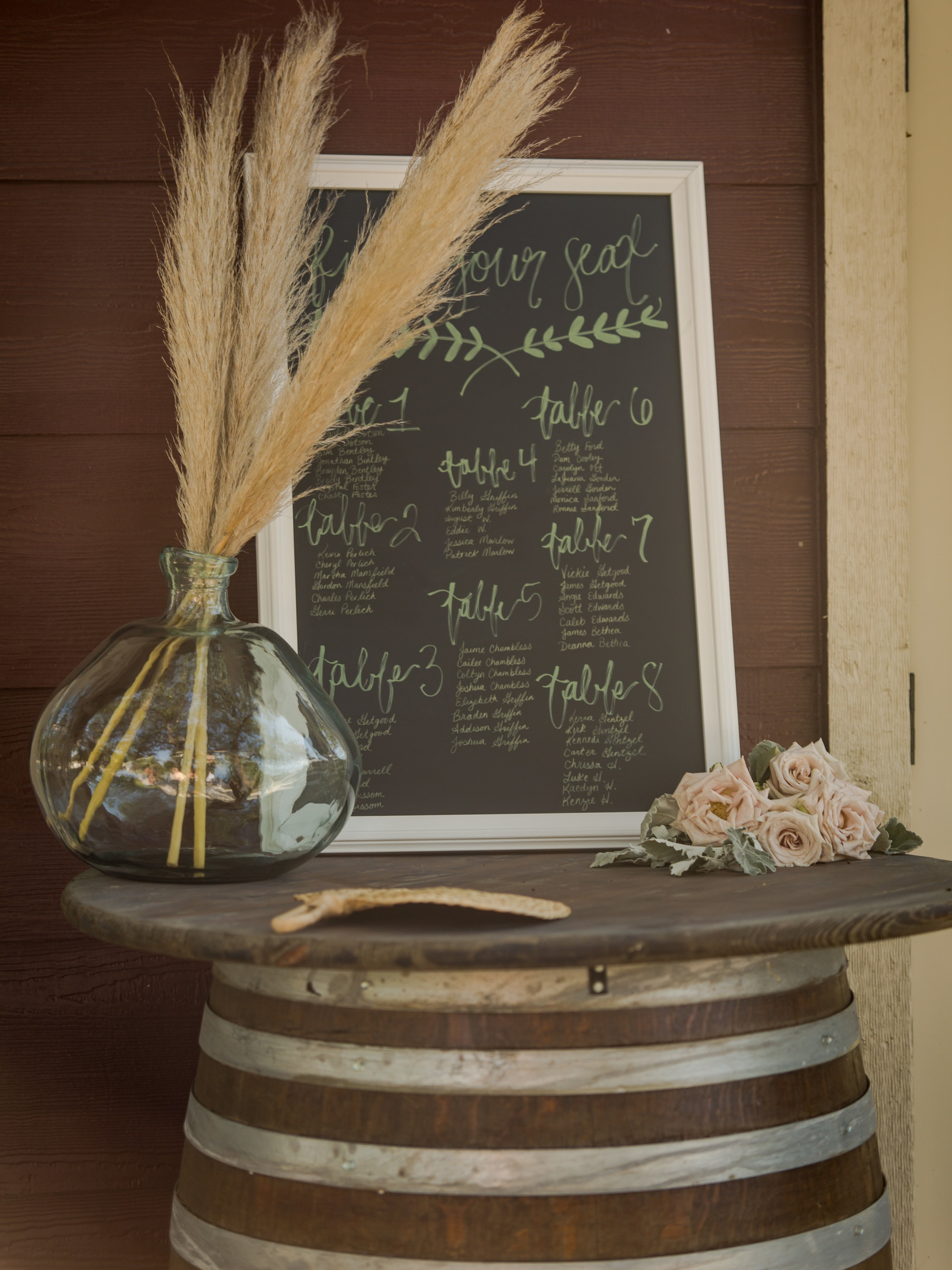 Wedding reception seat assignments drawn on a chalkboard and placed atop a wooden barrel.