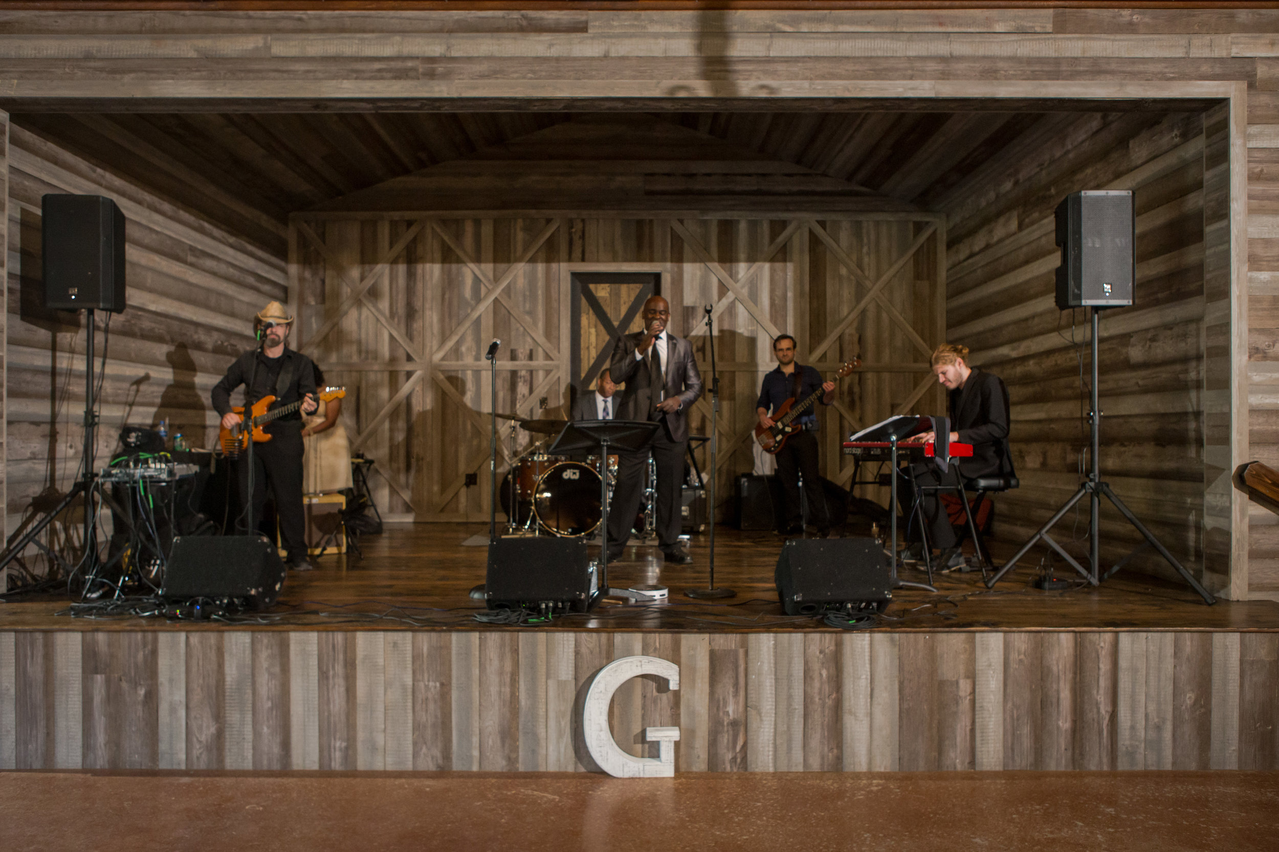 A wedding band performing on a wooden stage in a barn.
