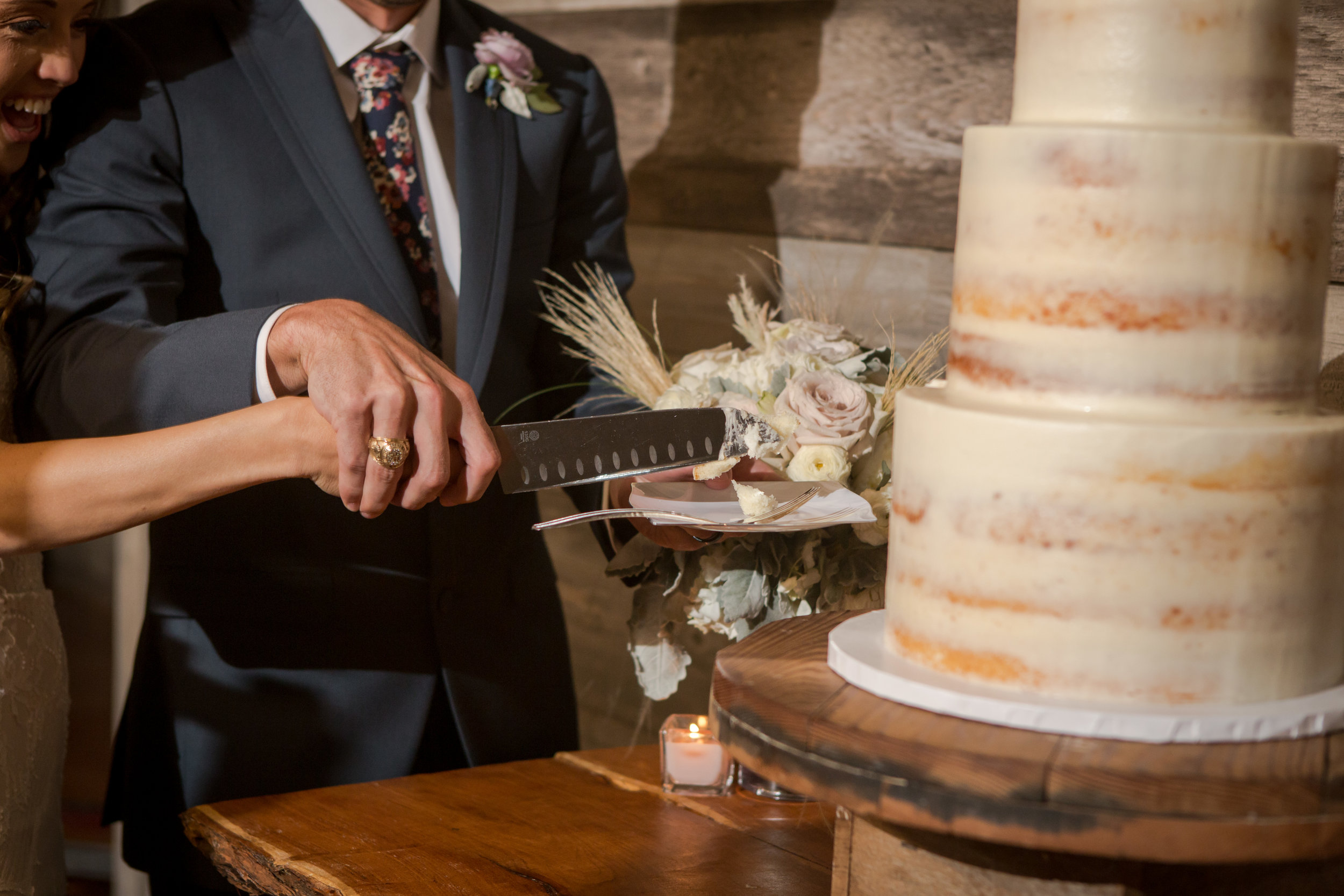 Bride and groom cutting their rustic wedding cake with unfinished white frosting.