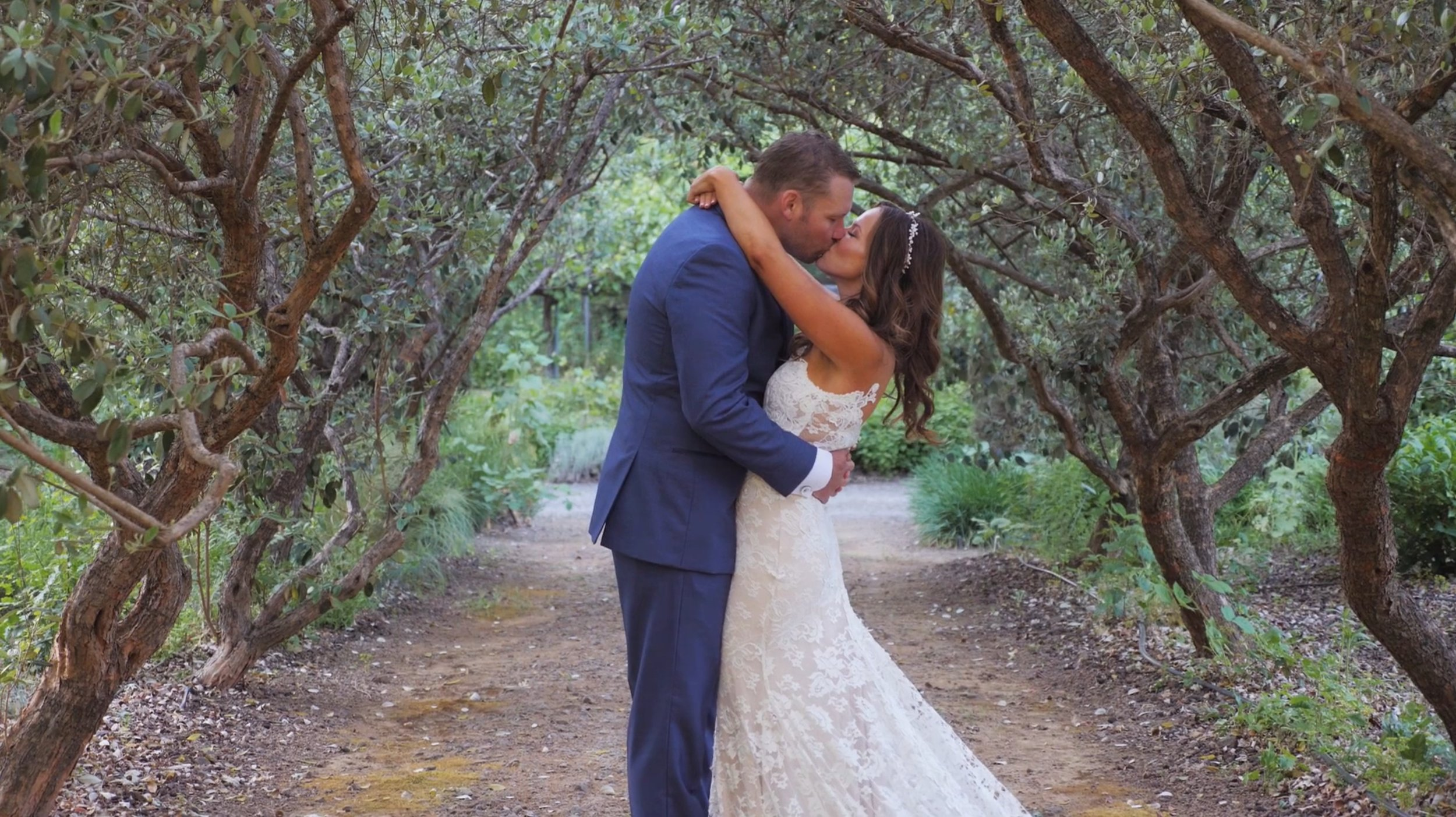 Groom kissing his bride on a natural trail between gnarled trees.