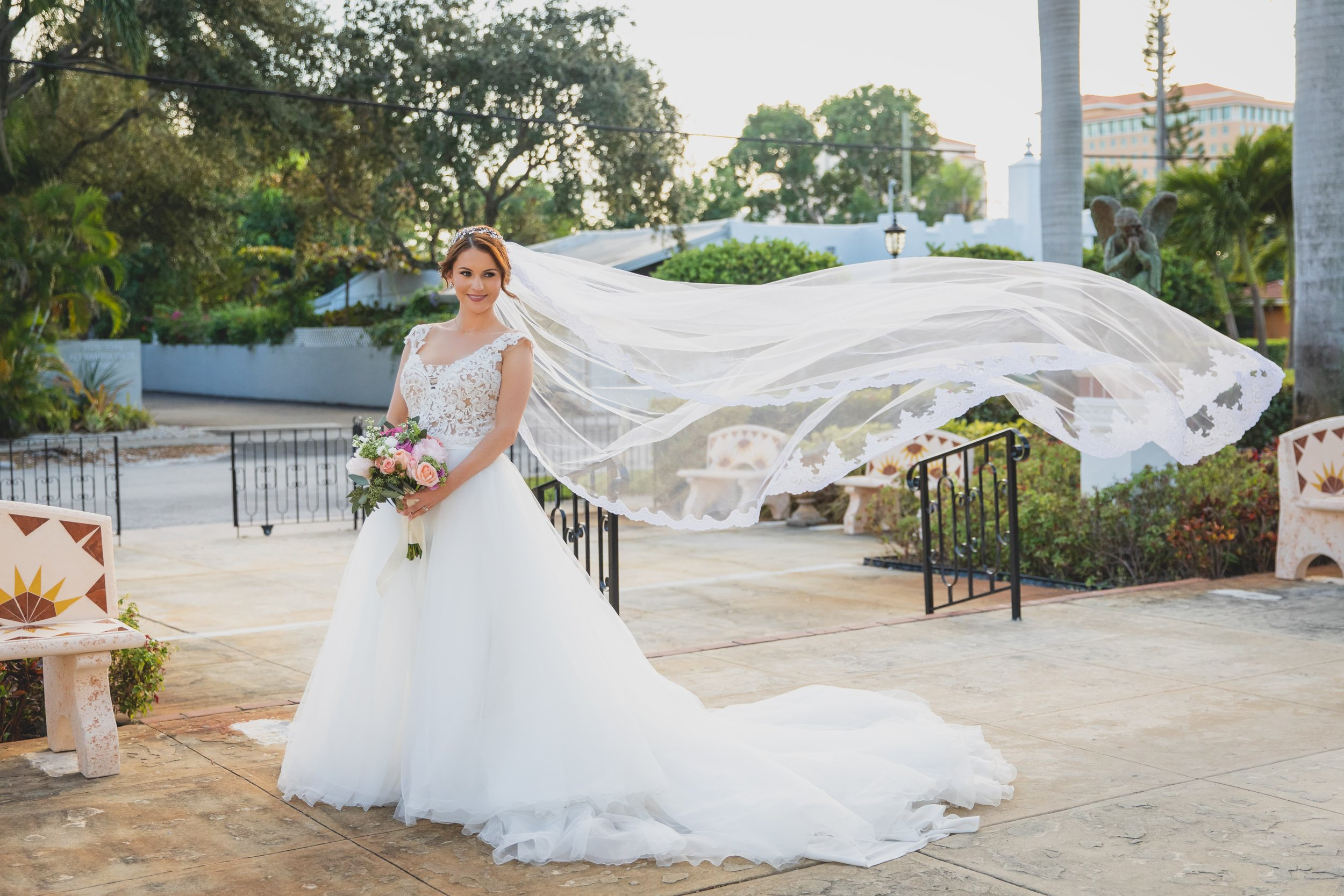 A bride in a flowing white dress with her veil flowing behind her in the wind.