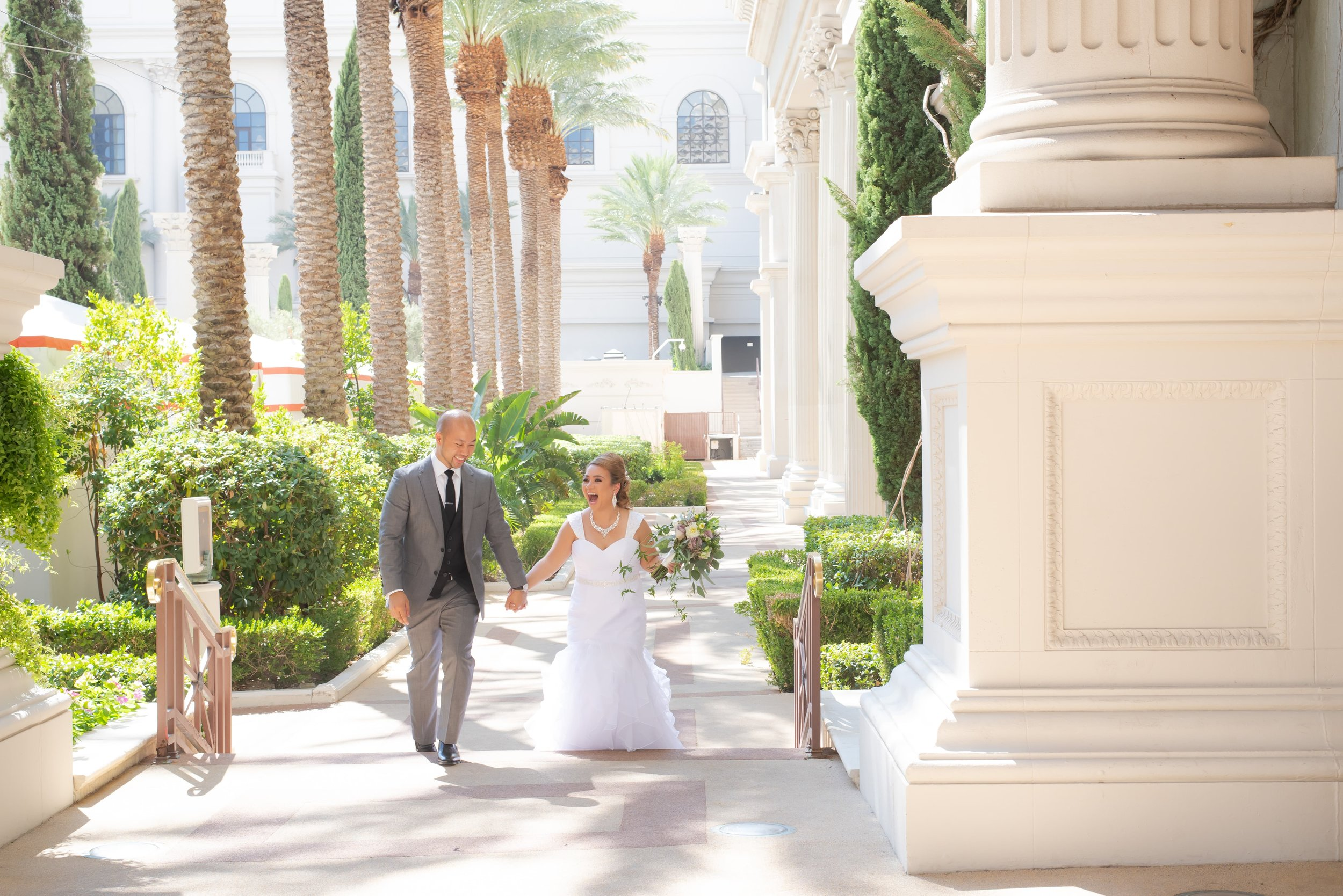Bride and groom walking up an outdoor staircase lined with palm trees and stone pillars.
