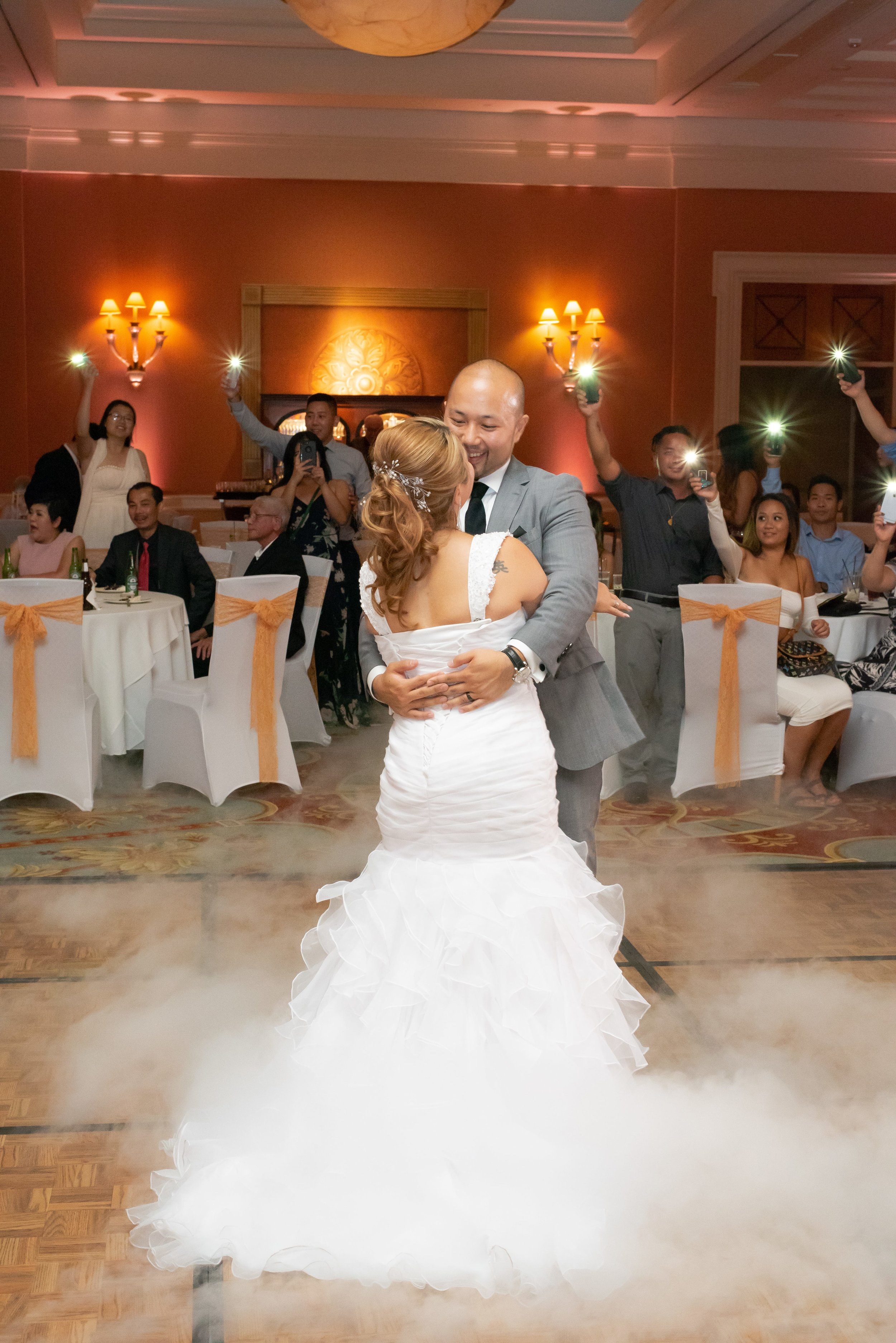 Bride and groom sharing a dance while their guests record them with their phones.
