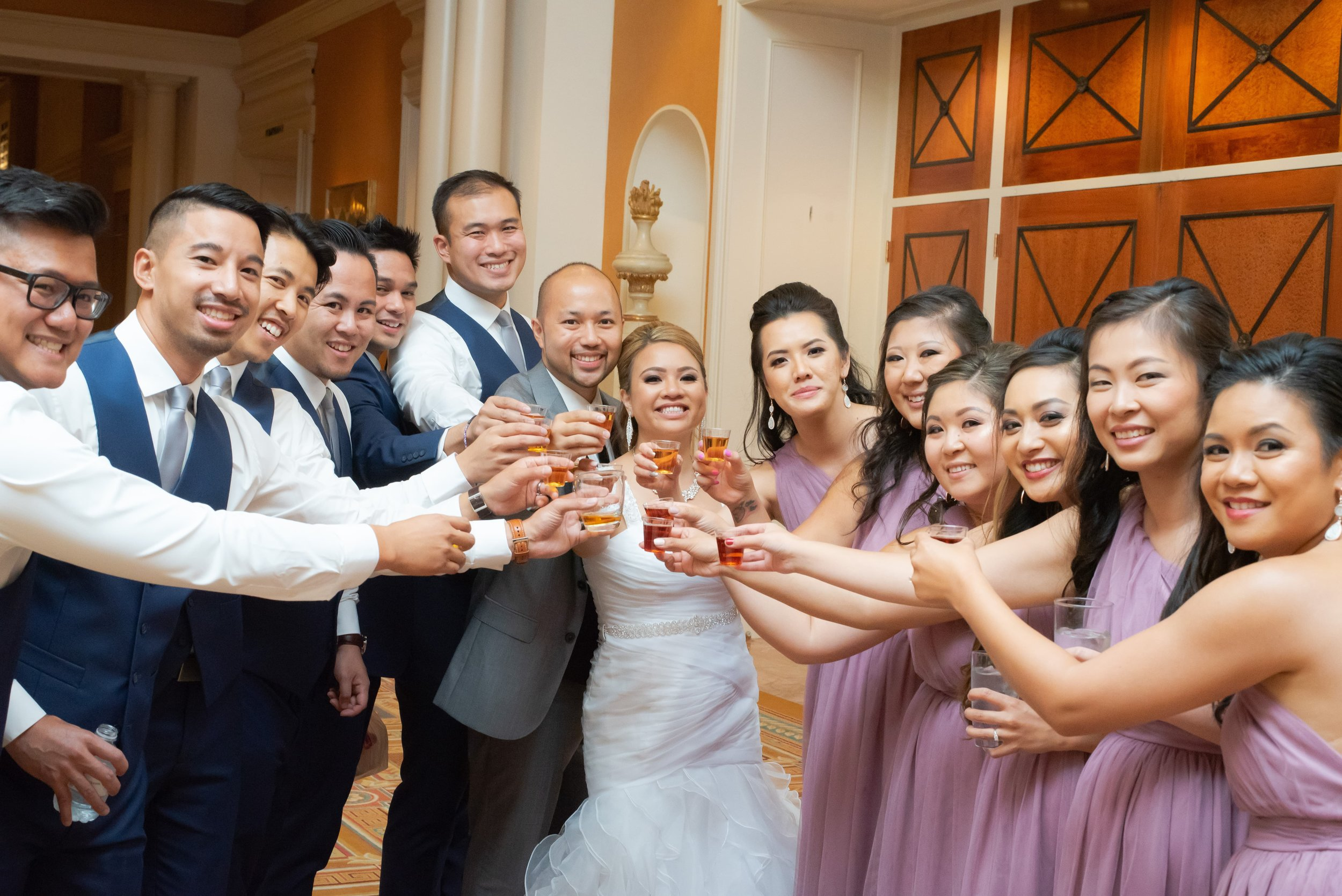 The wedding party toasting while smiling for the camera.