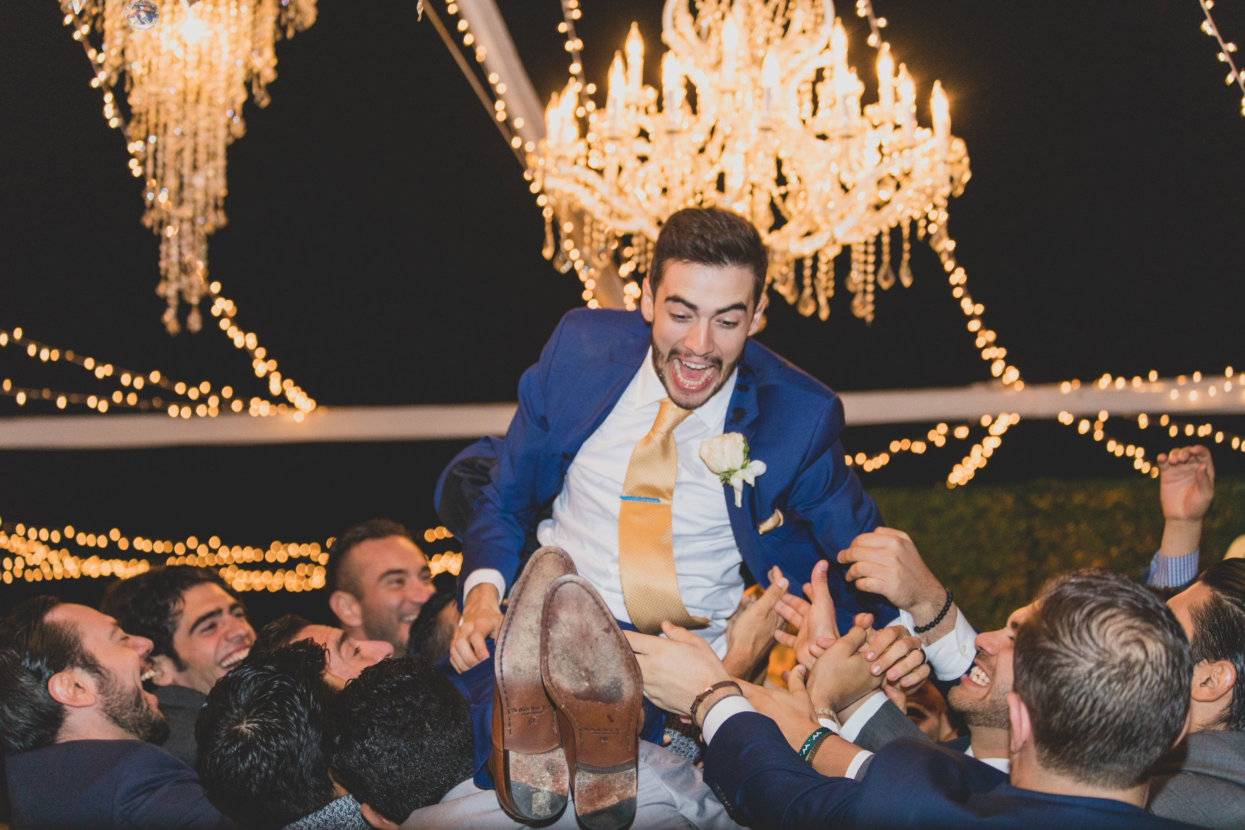 Groom being lifted in the air by his groomsman.