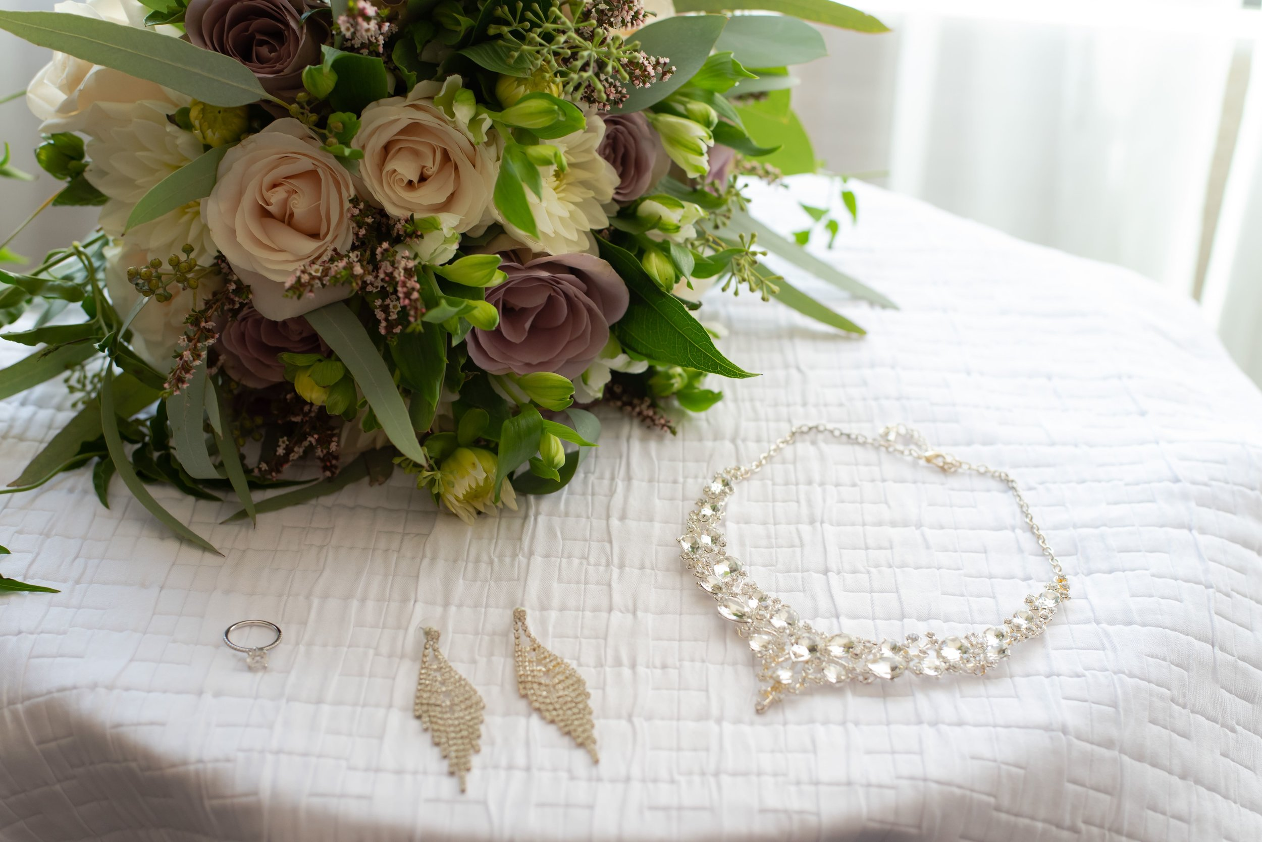 A necklace, earrings, an engagement ring, and a bouquet on a round table with a white tablecloth.