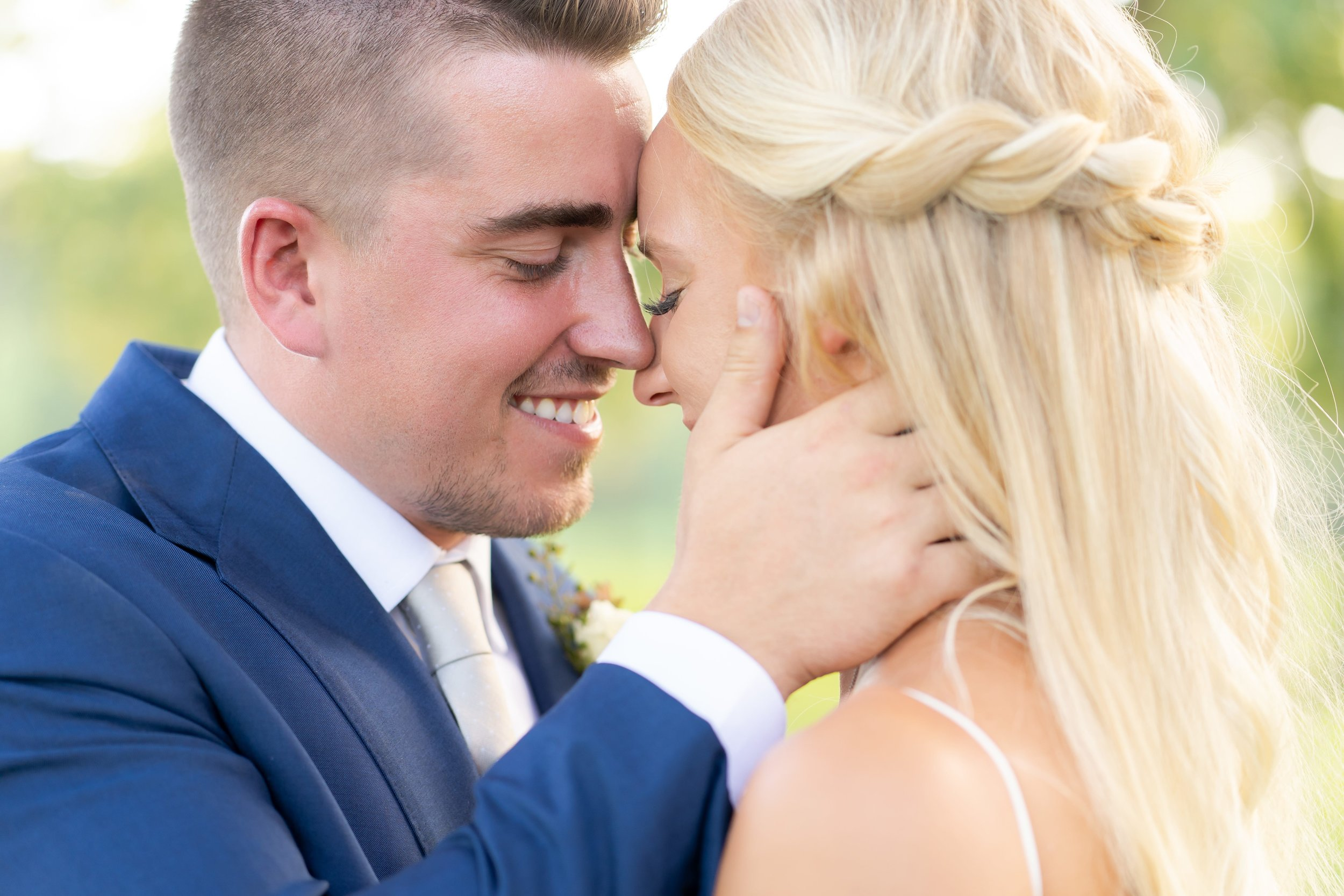 A bride and groom leaning in and touching noses in an intimate gesture.