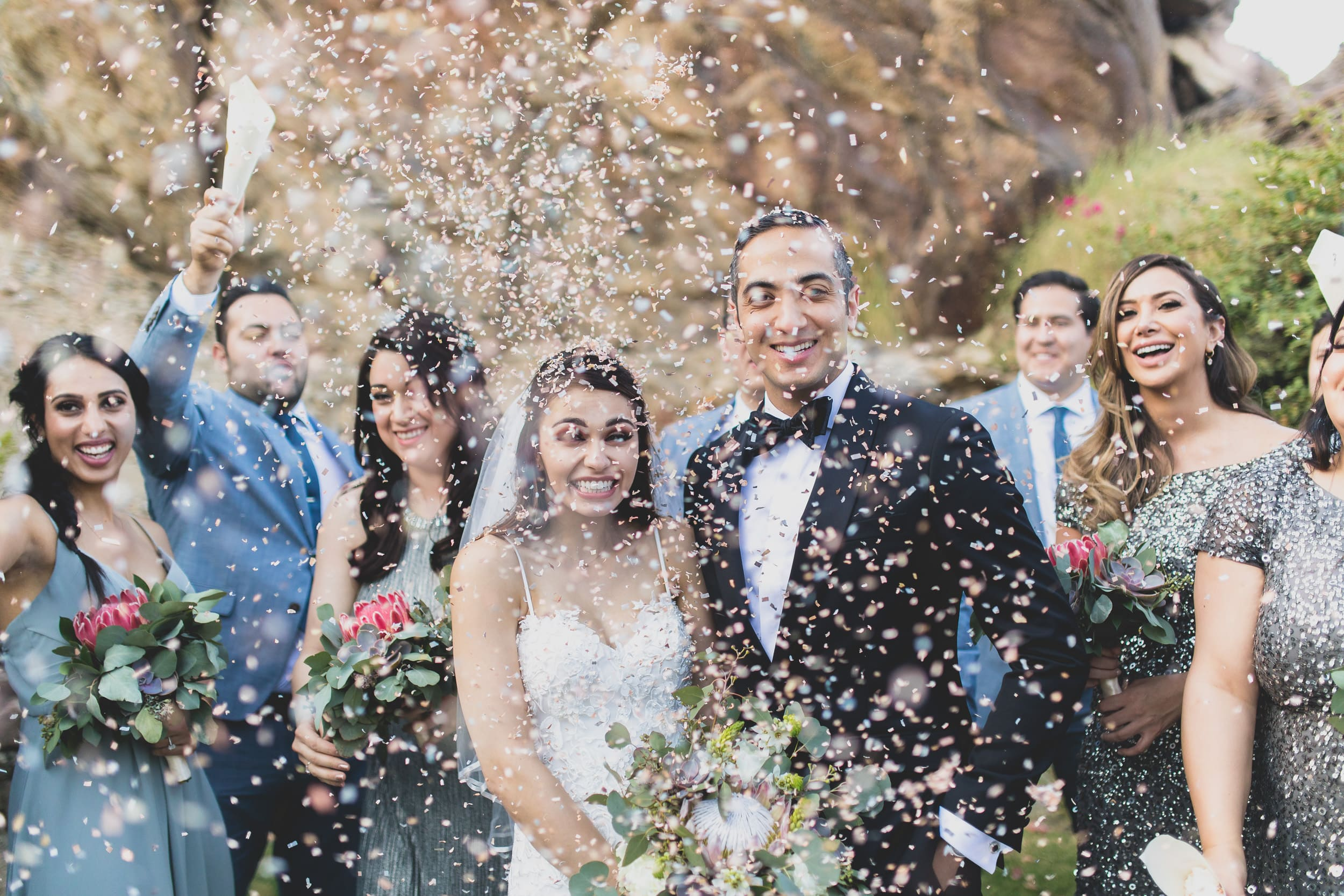 Bride and groom smiling with their bridal party as confetti rains down upon them.