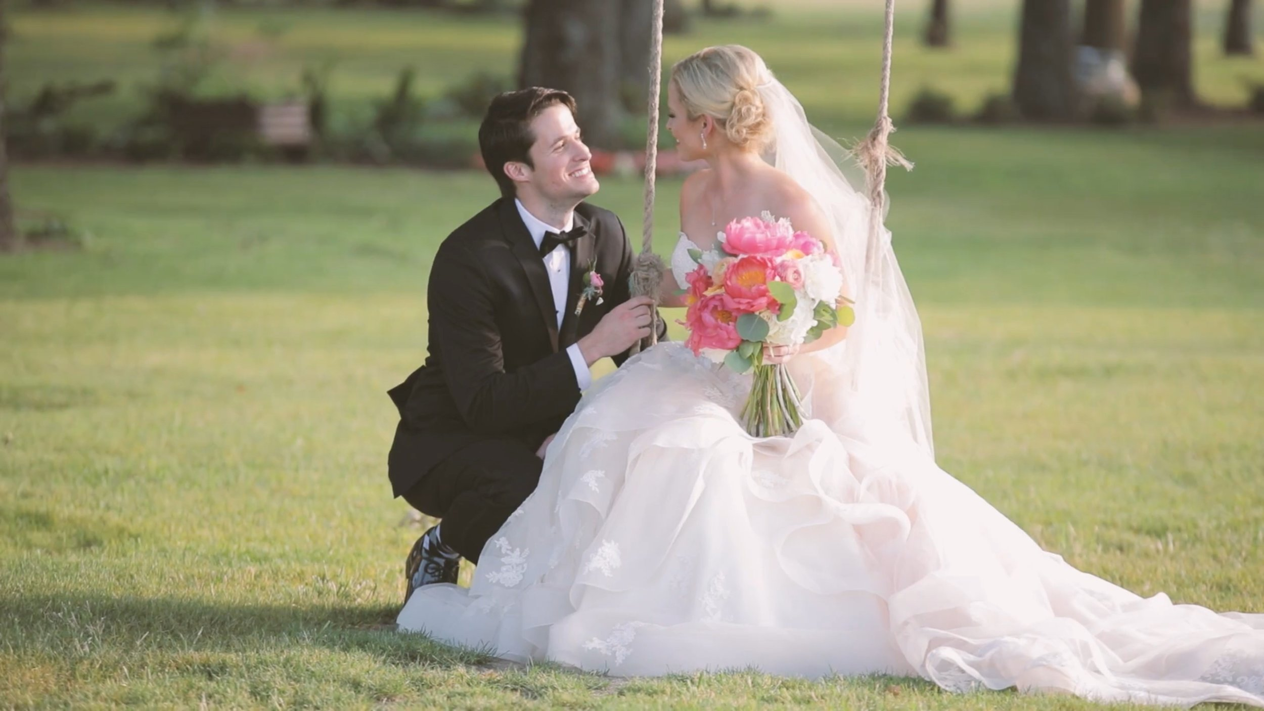 Bride sitting on a wooden sing with a bouquet of pink flowers while her groom kneels beside her.