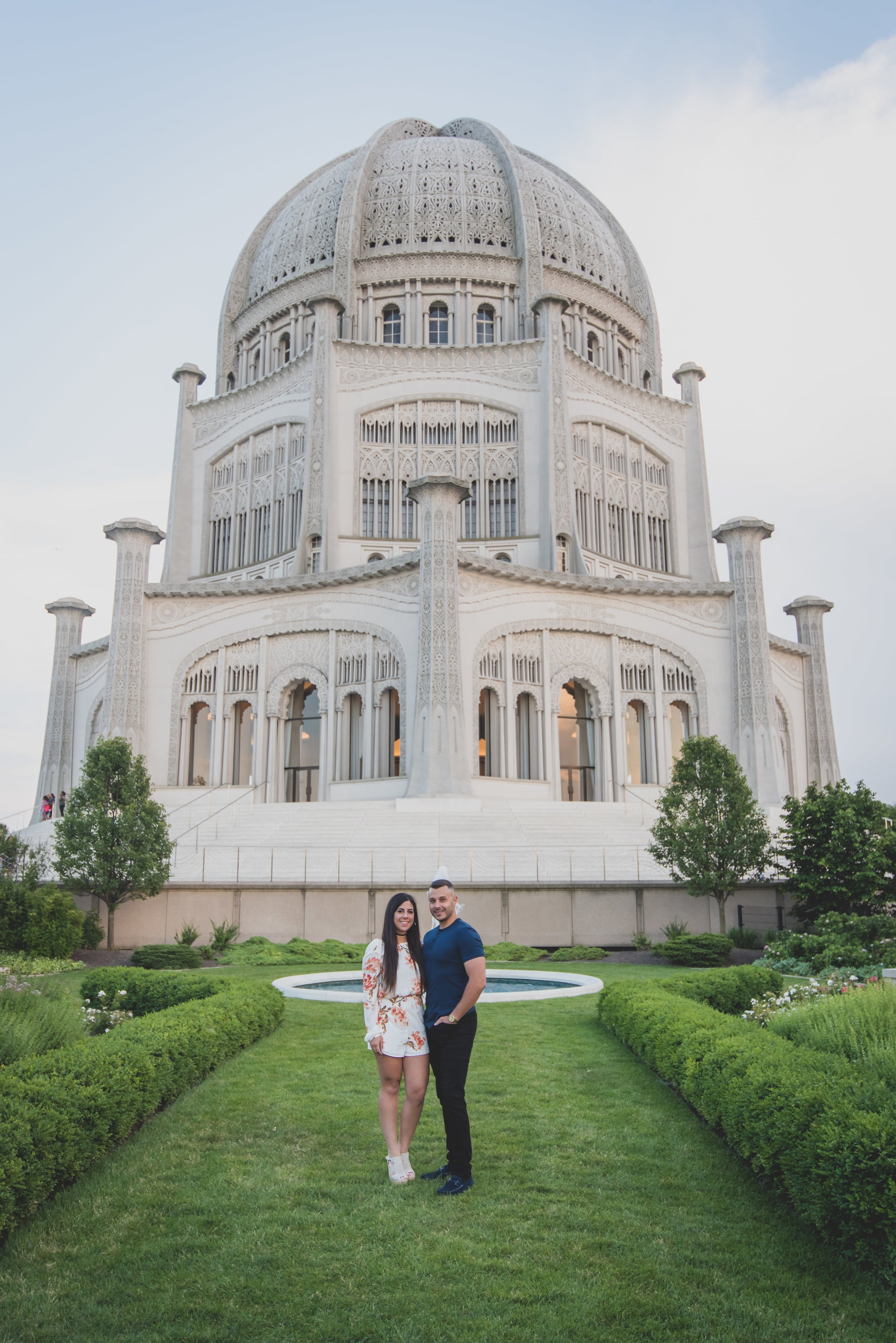 Engaged couple standing on landscaped lawn in front of the baha'i temple.