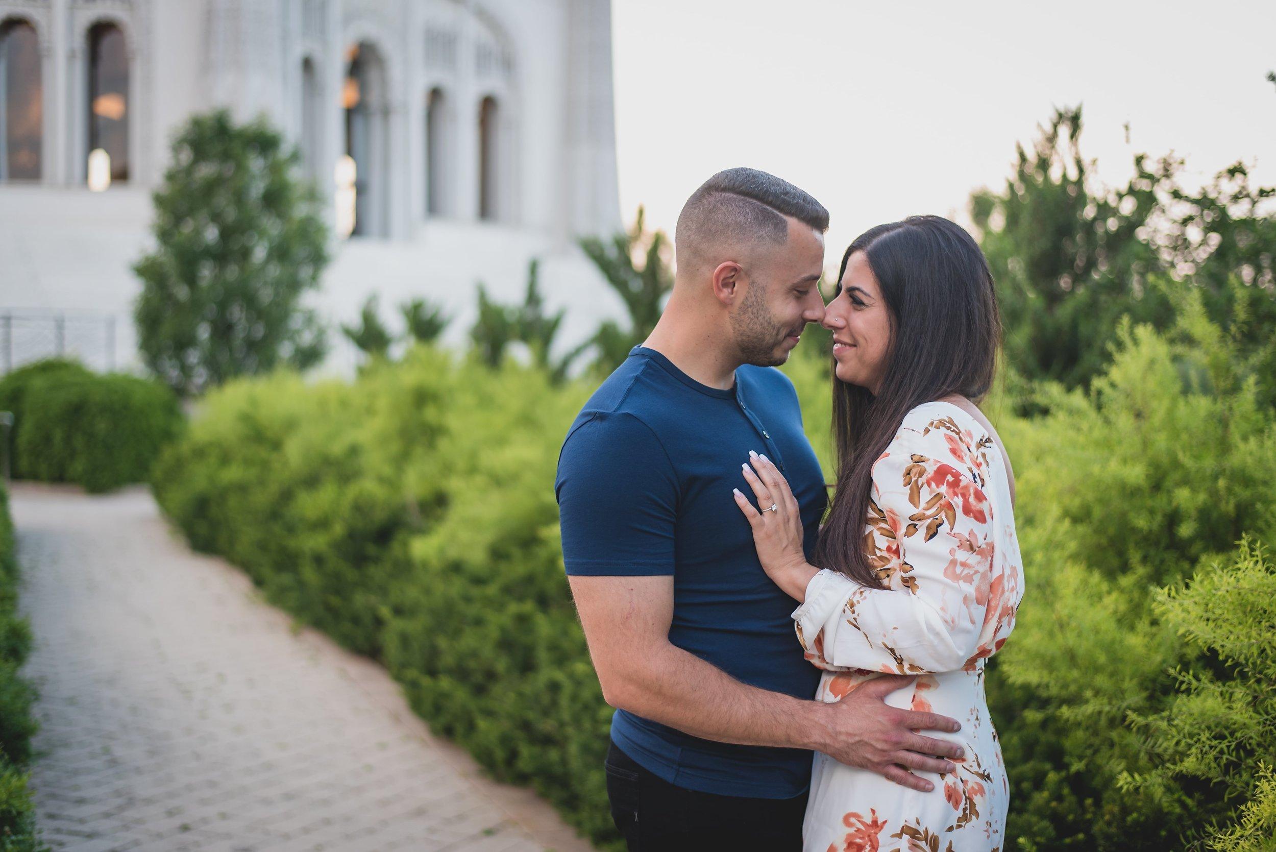 Engaged couple on stone pathway kissing.