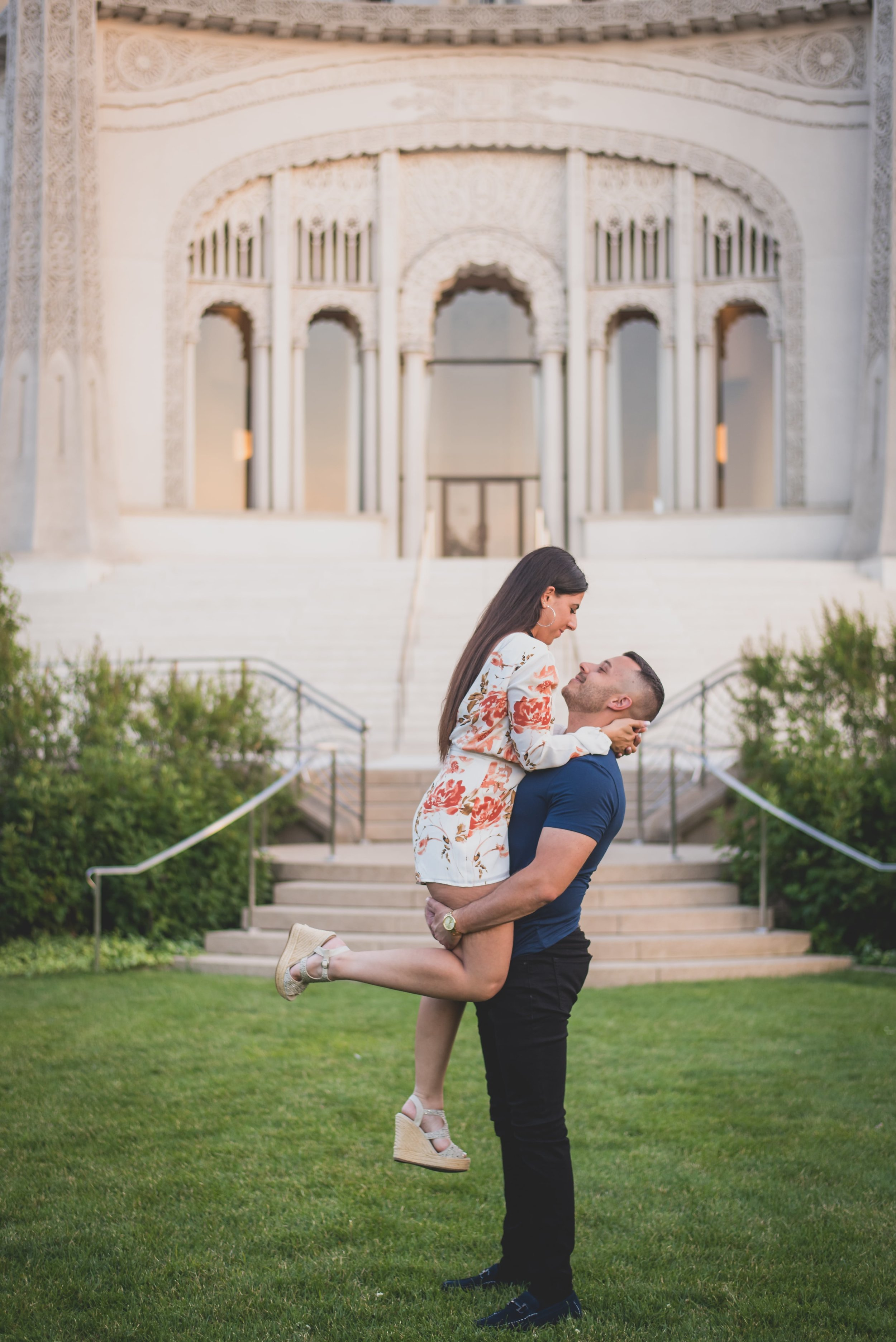 Man carrying his fiance in front of a stone temple.