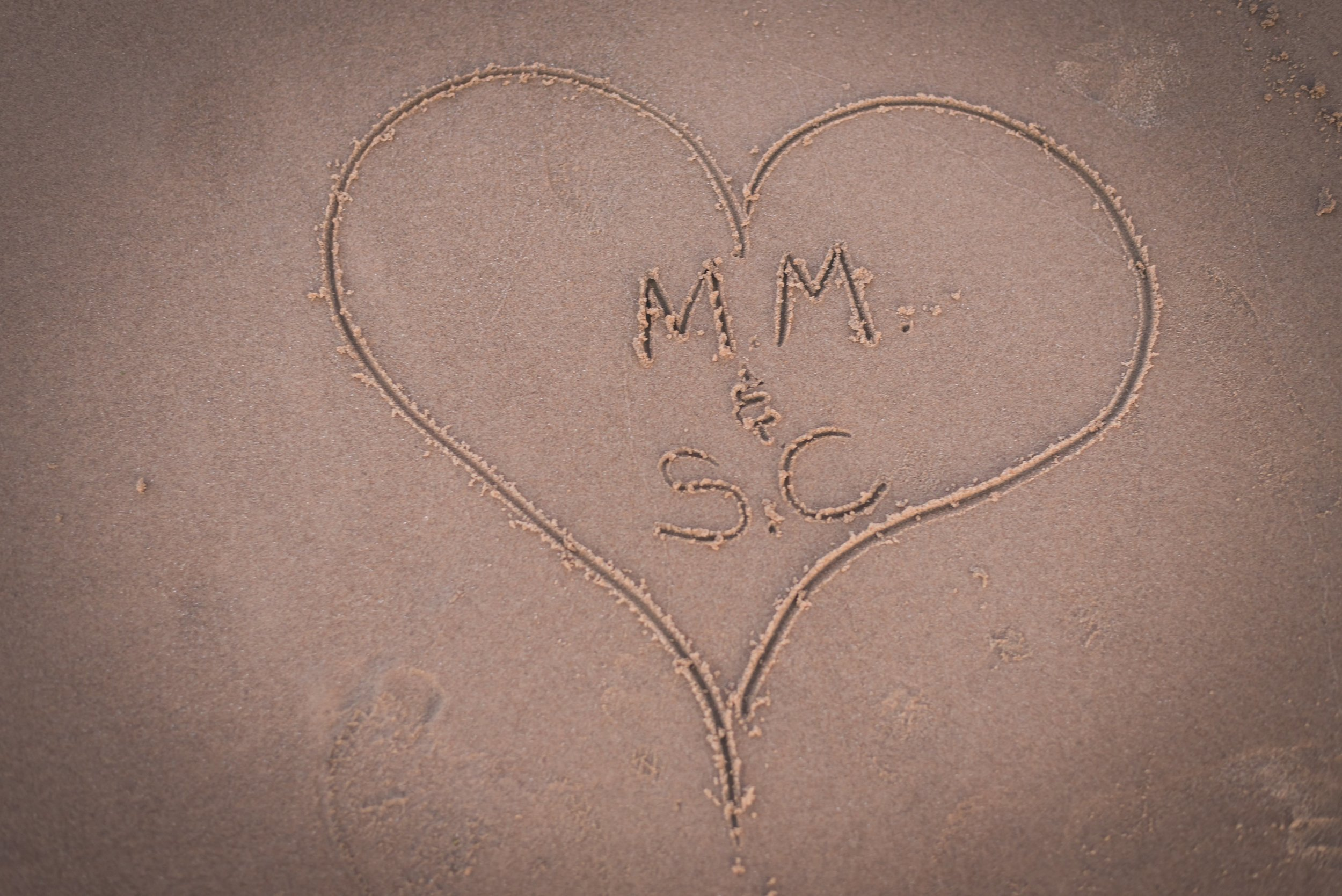 A couples initials etched in the sand surrounded by a heart.