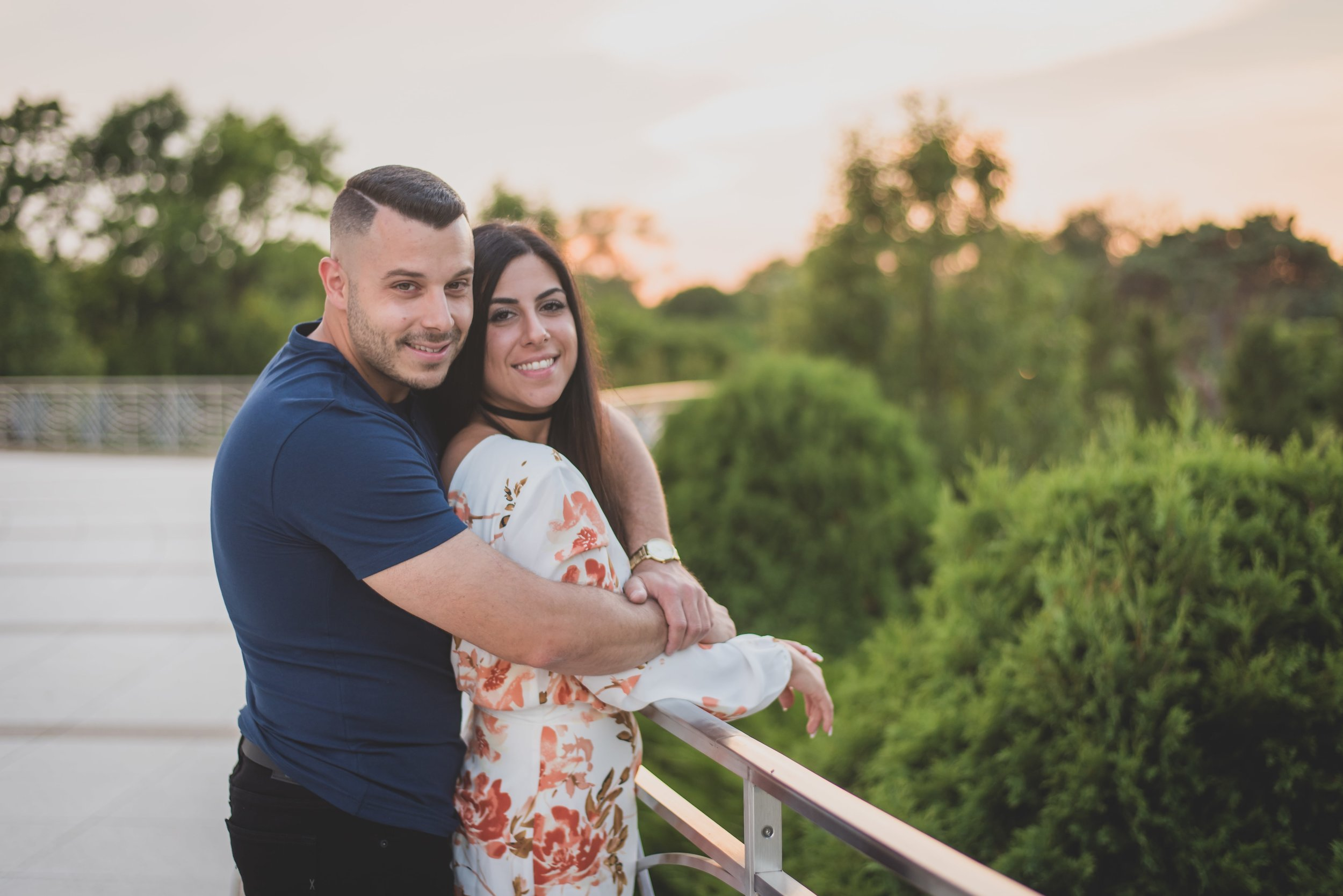 Engaged couple embracing on a rooftop.