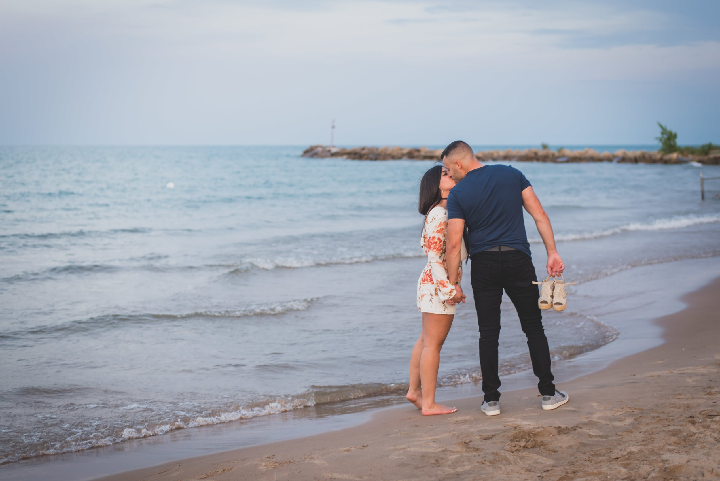 Man carries woman's shoes as they kiss on the beach.