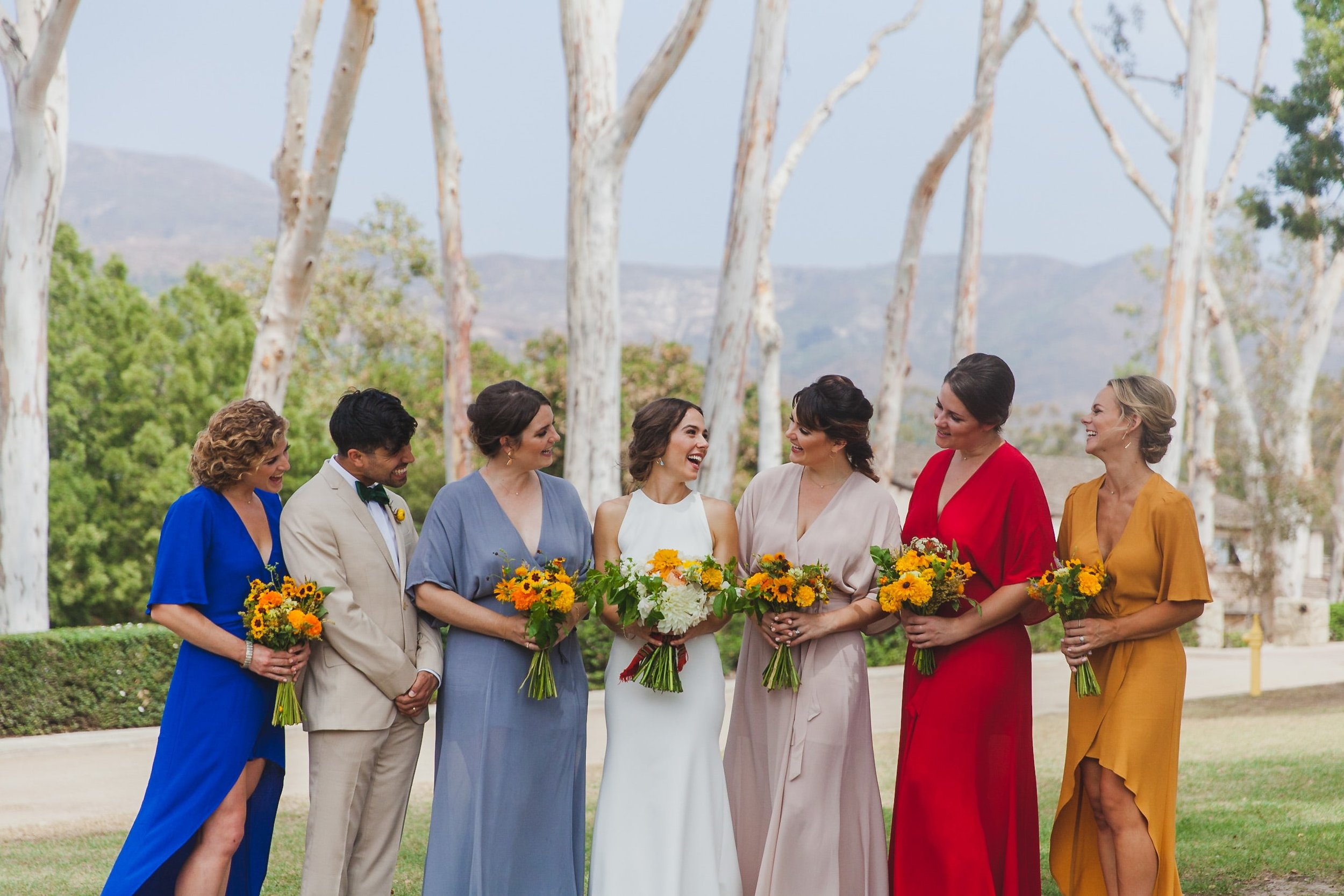 Bridesmaids in colorful dresses flanking the smiling bride.