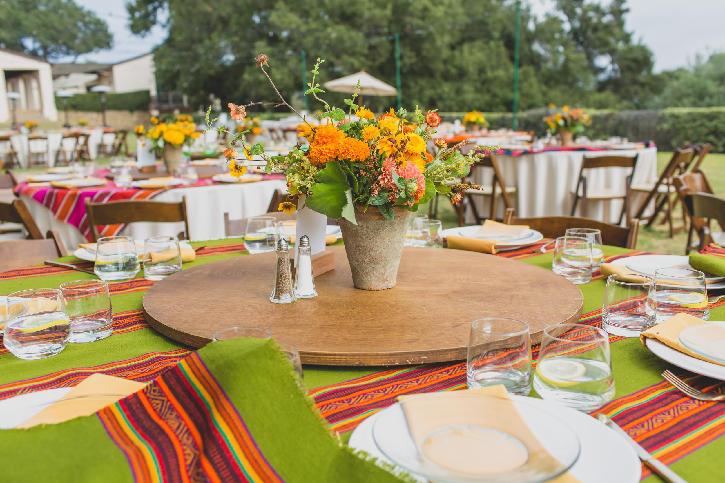 Wedding reception tables with cambaya tablecloths and wildflower centerpieces in stone vases.