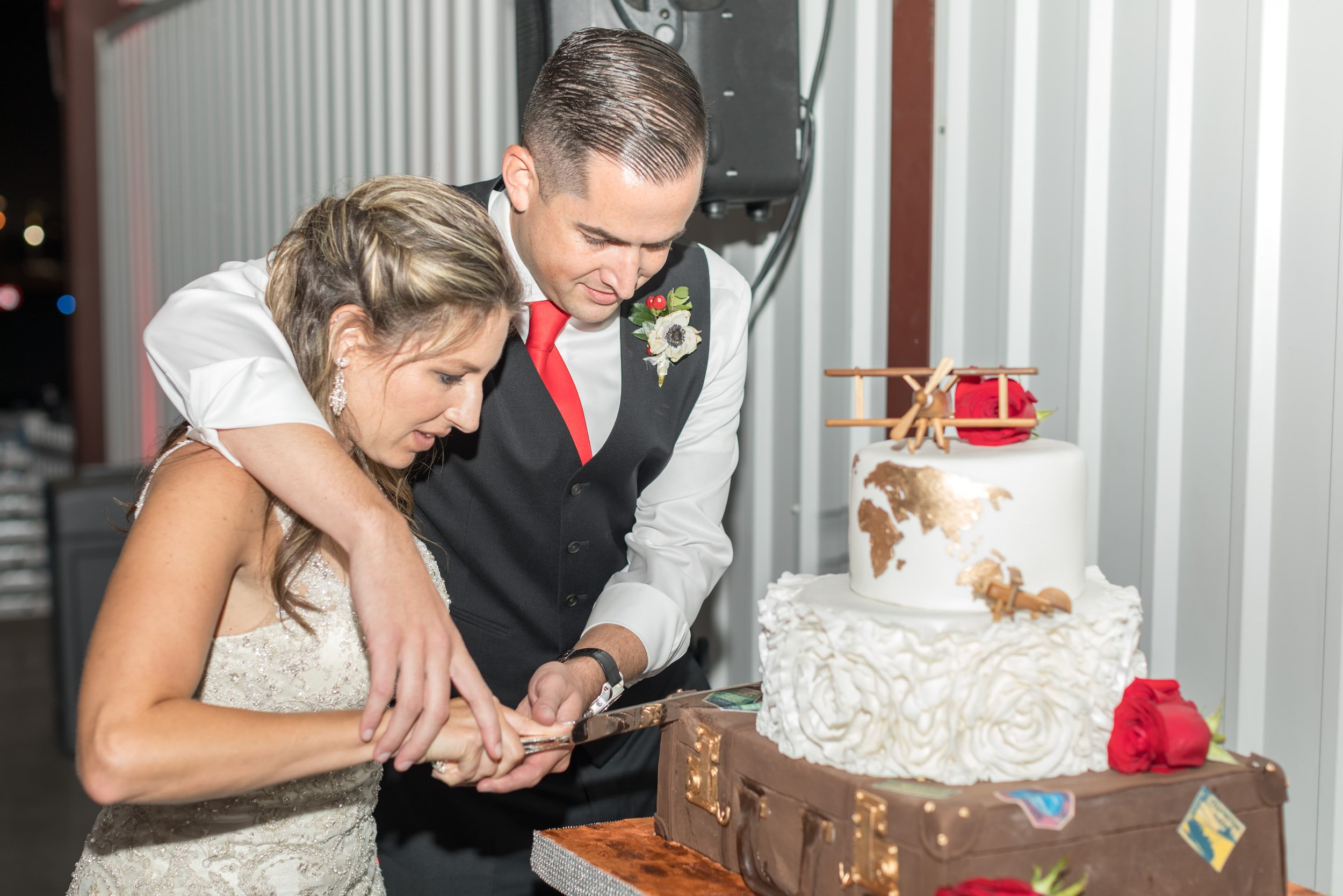 Bride and groom cutting their aviation themed wedding cake.