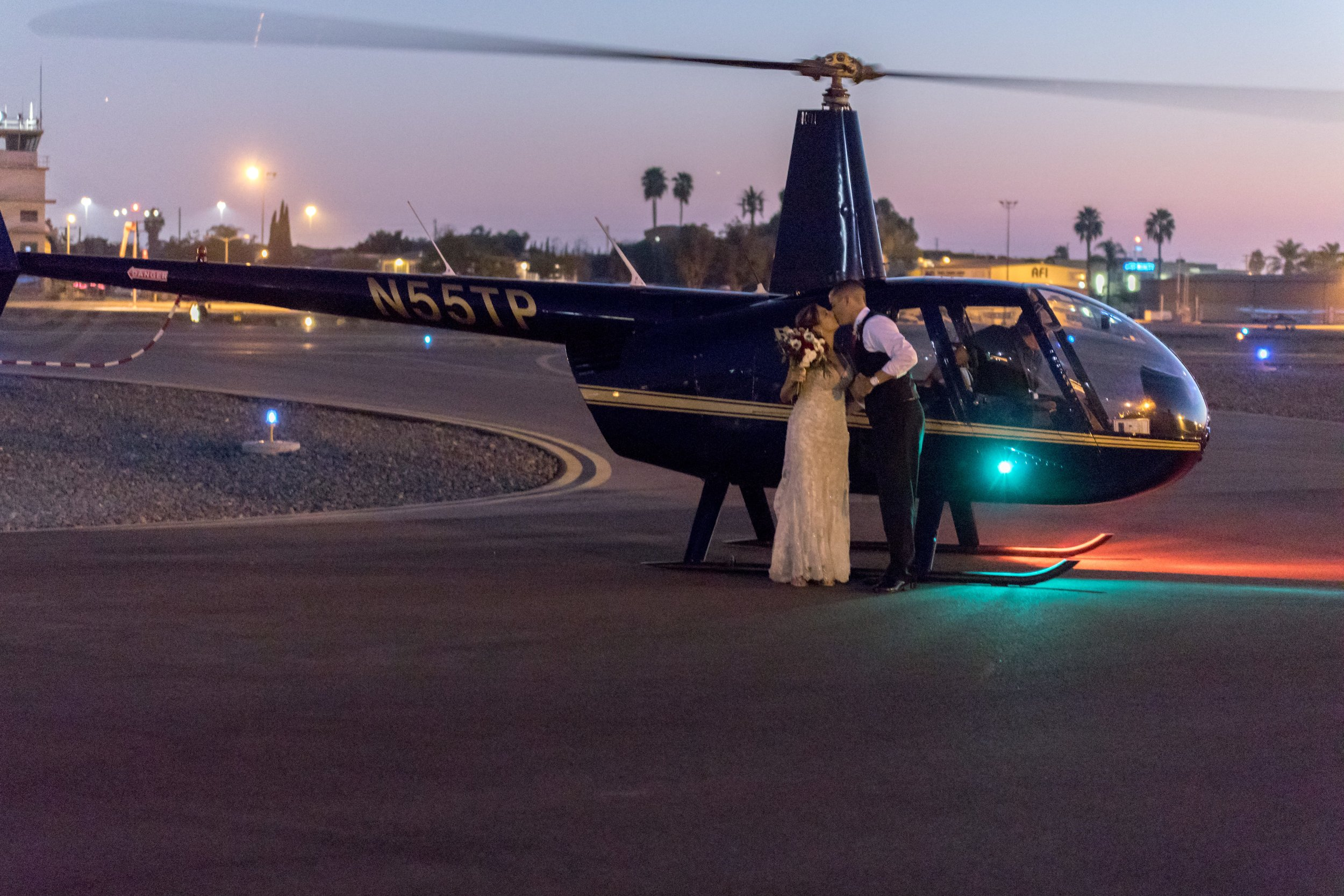 A bride and groom depart by helicopter for their aviation wedding themed grand exit.