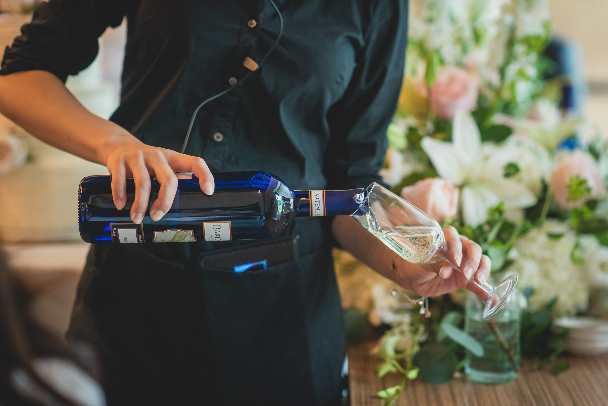 A bartender pouring a glass of wine.