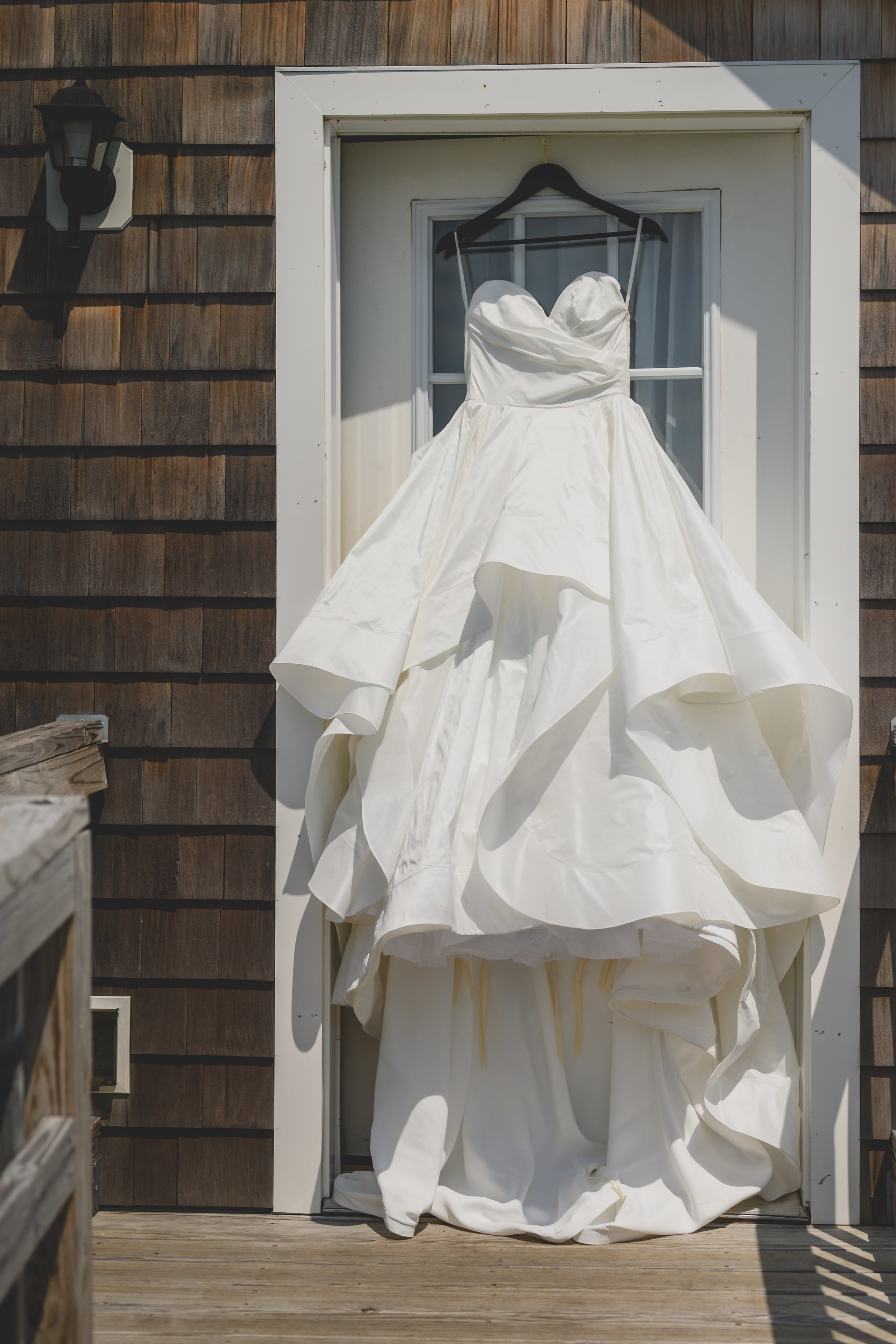 Wedding dress hanging outside from a white door.