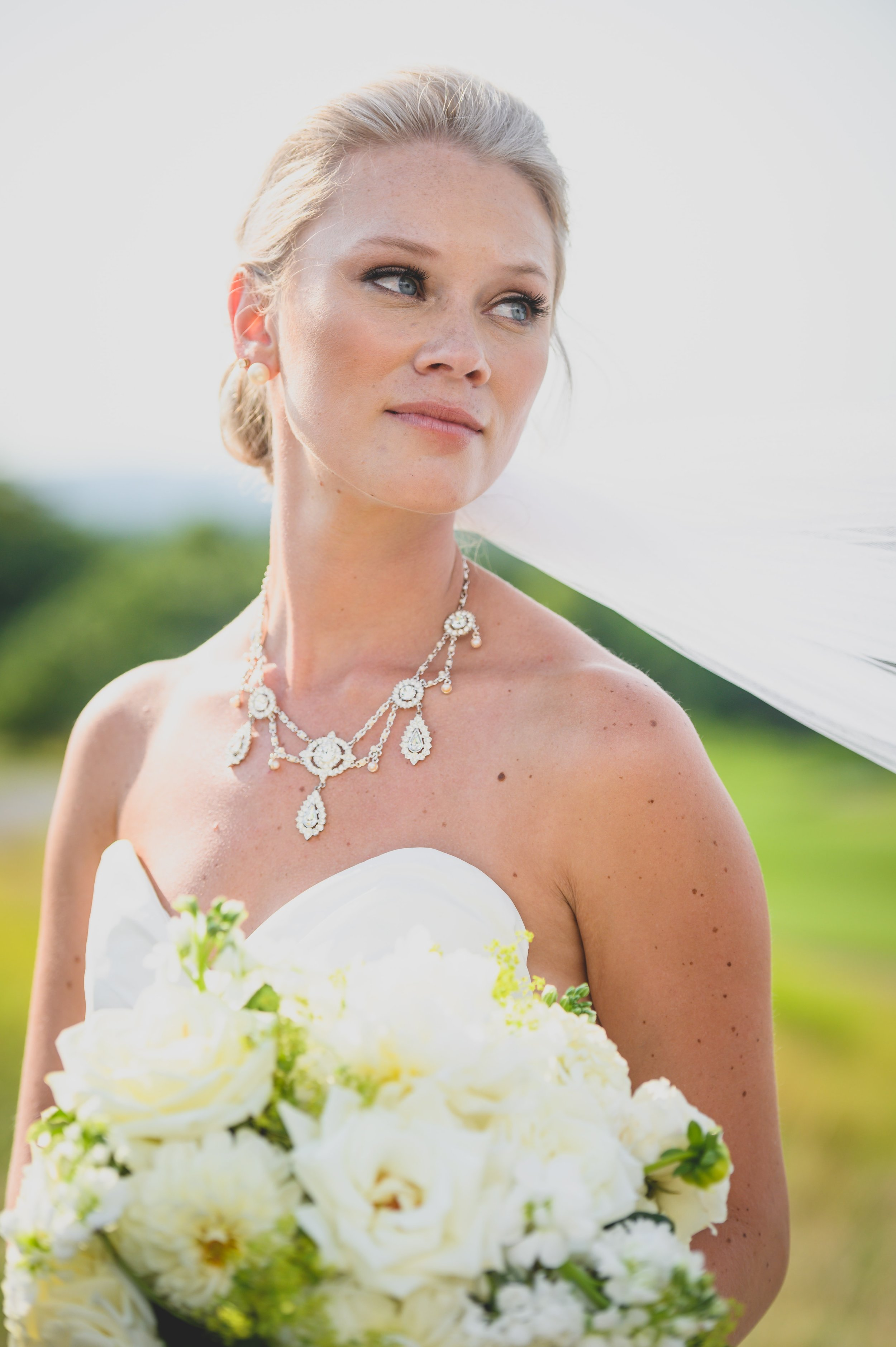 A bride holding a bouquet of flowers with her veil blowing in the wind.