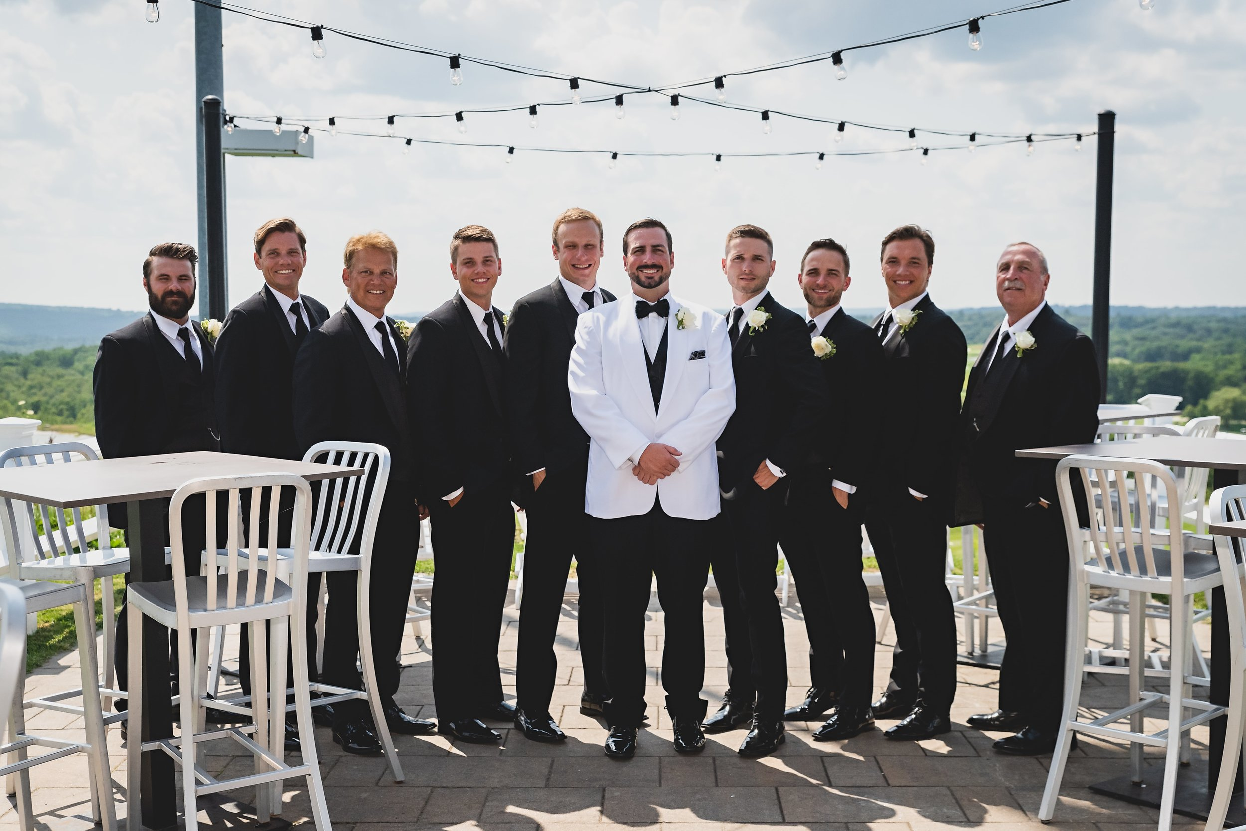 A groom in a white tuxedo flanked by his groomsman in black tuxedos.