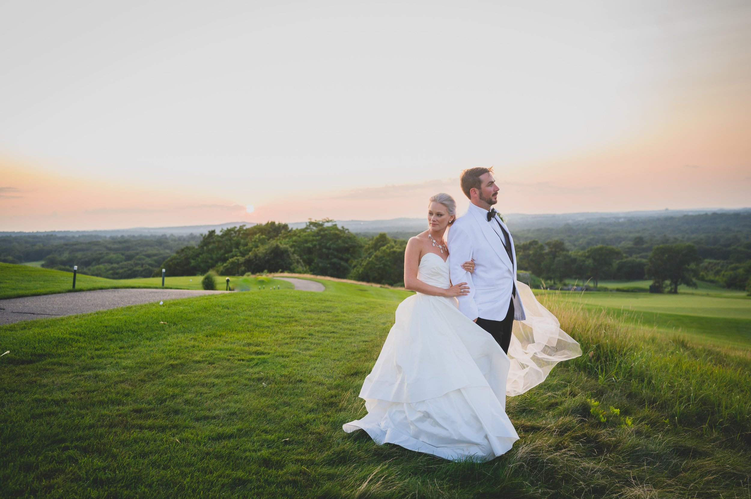 A groom in a white tux with his bride in an open field of green.