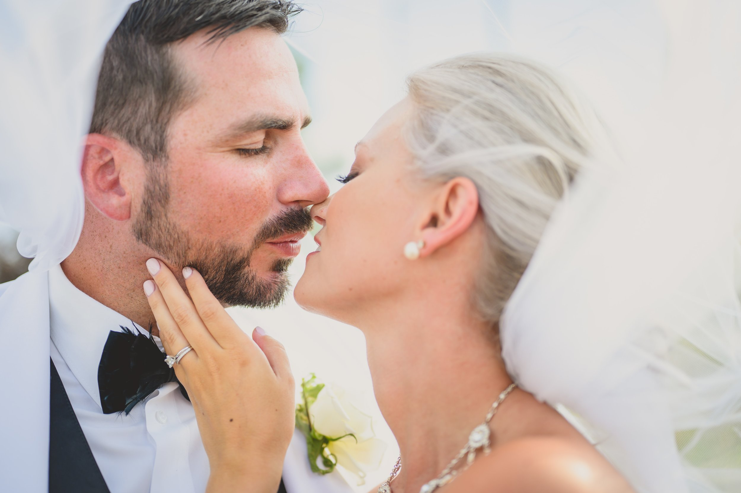 A groom and bride kissing under her wind blown veil.