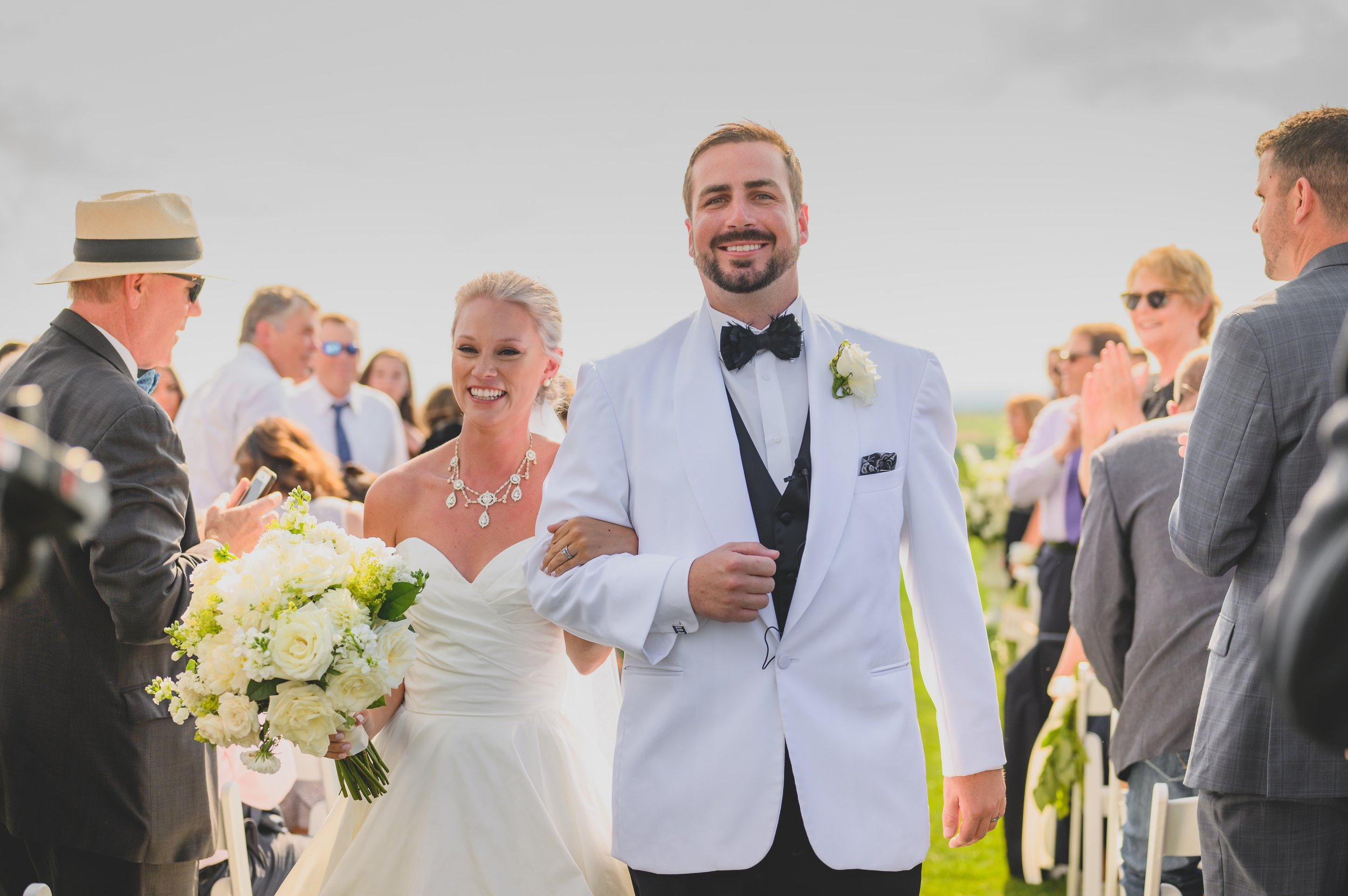 A groom in a white tux and his bride exiting their outdoor ceremony.