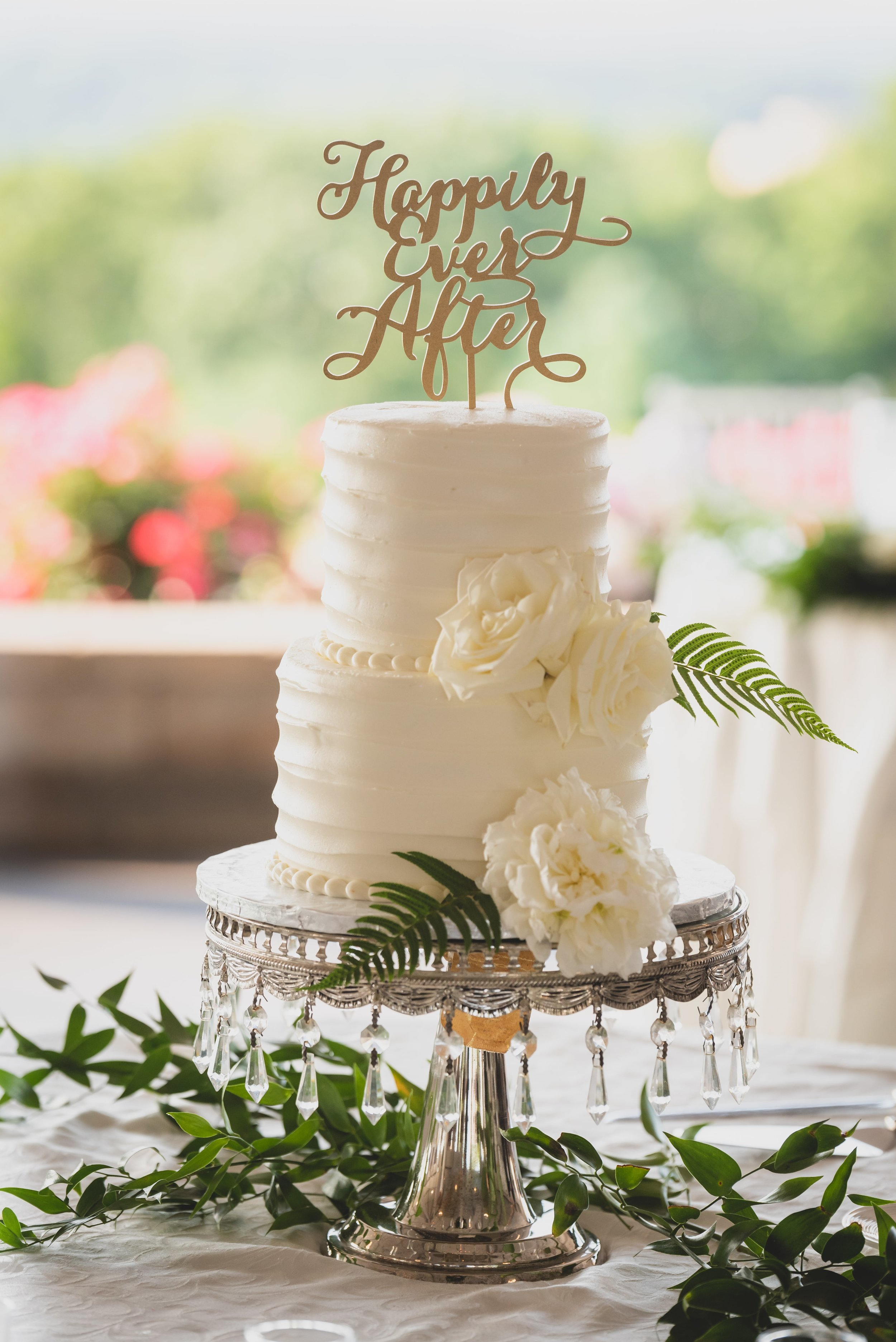 An all white wedding cake with green leaves and white roses.